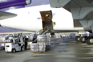 Plastic-wrapped bales of blankets are loaded onto conveyer belts on the tarmac at the Salt Lake International Airport. Some 8,000 blankets were included in the recent humanitarian shipment.