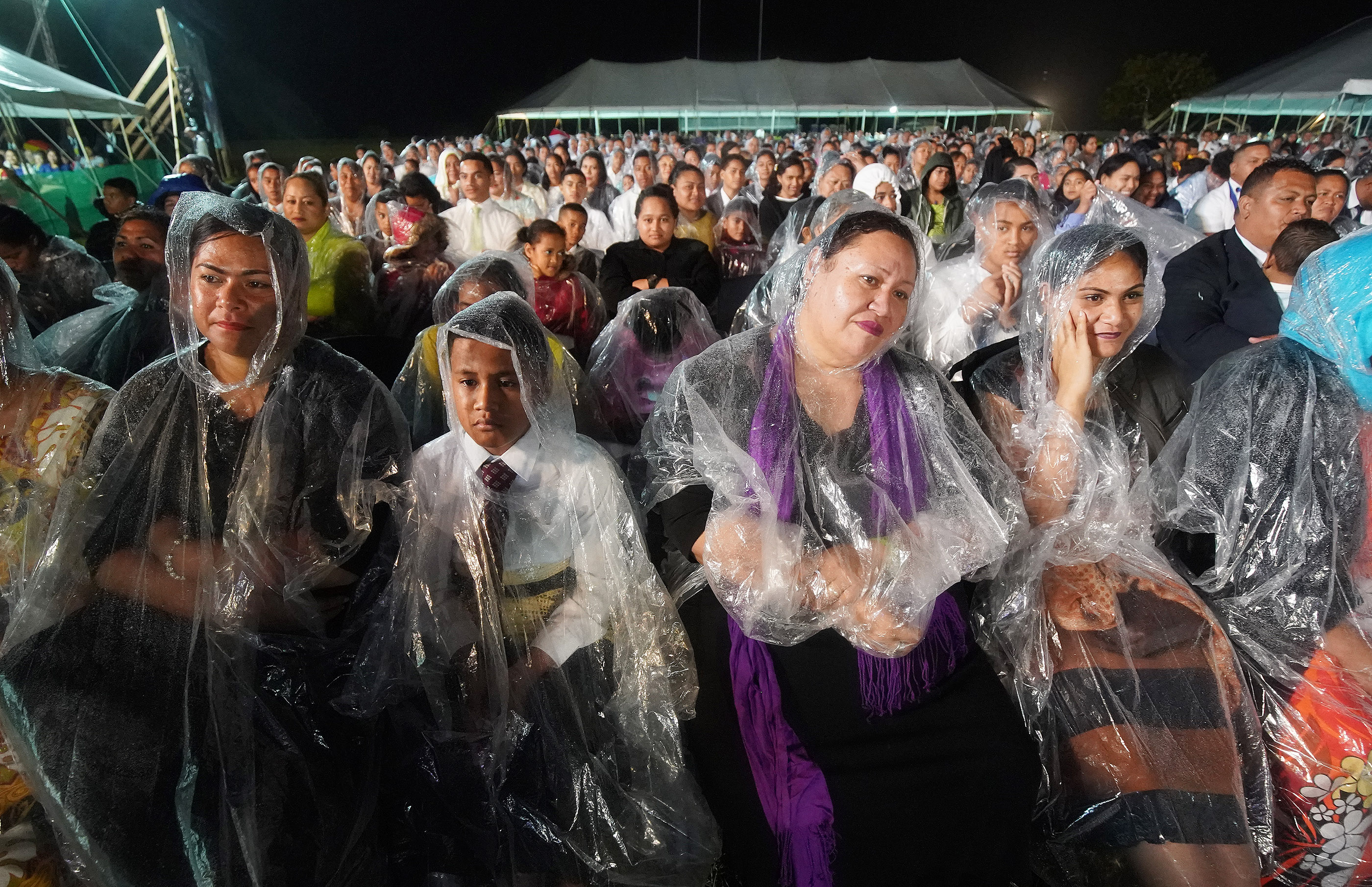Attendees sit in the rain during a devotional in Nuku'alofa, Tonga, on May 23, 2019.