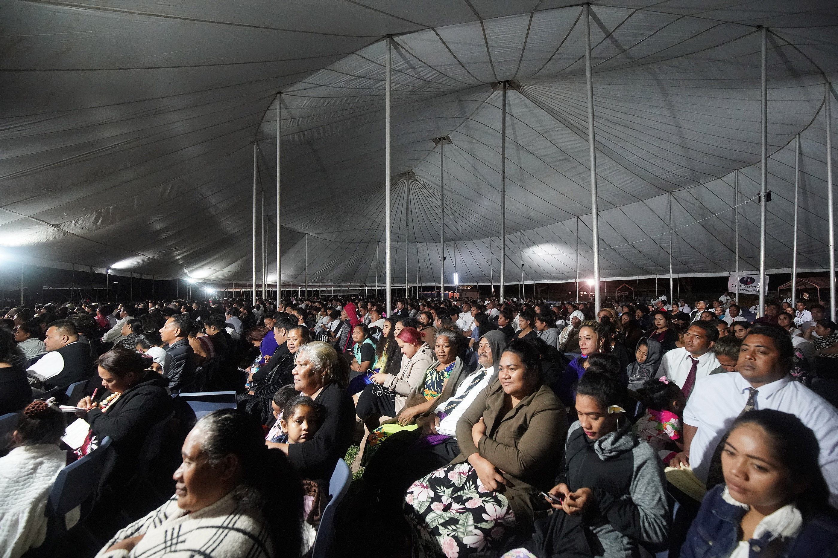 Attendees avoid the rain under a tent during a devotional in Nuku'alofa, Tonga, on May 23, 2019.