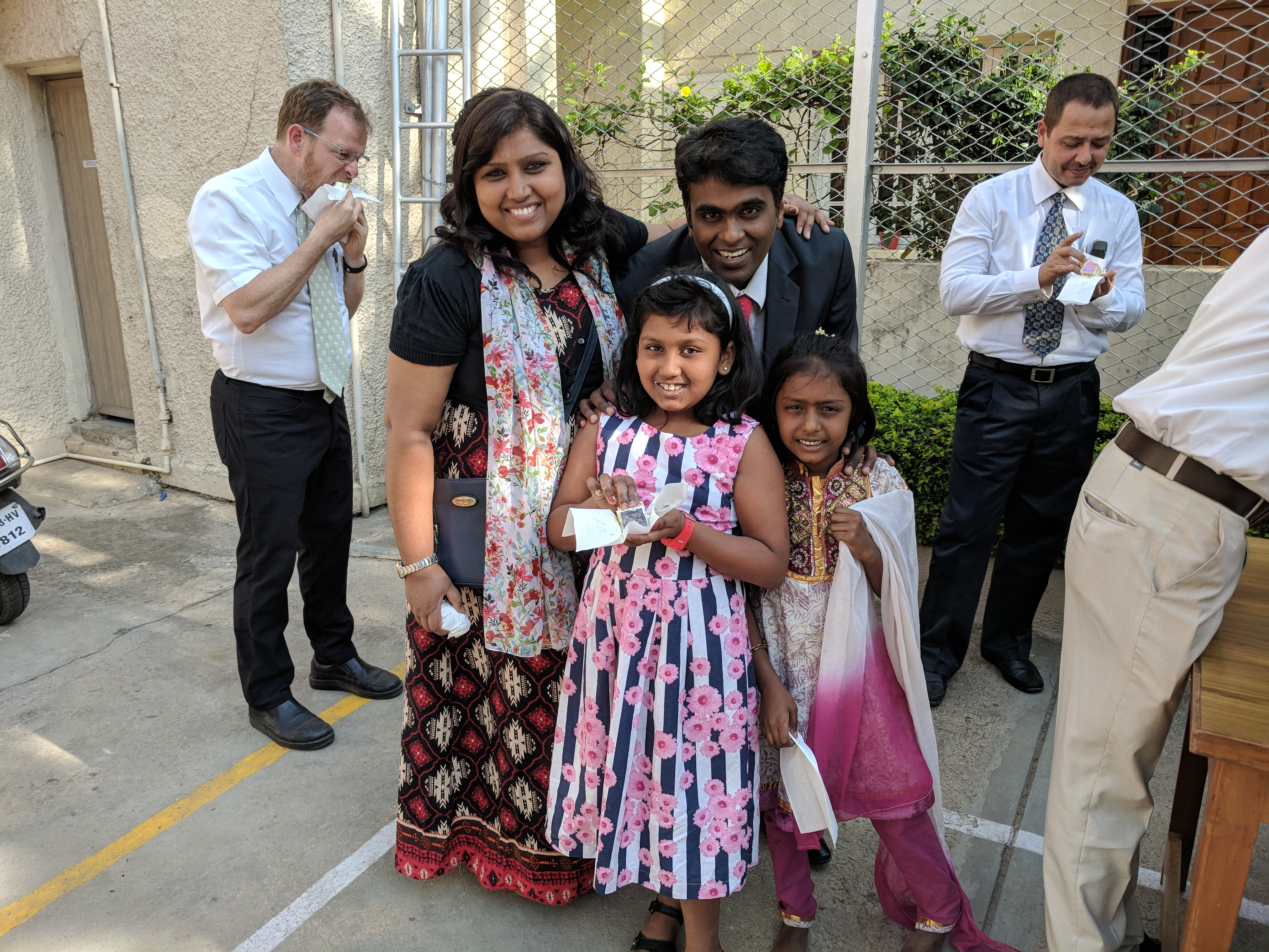 Members in Bangaluru India celebrate with cake after hearing the announcement of a temple in India.