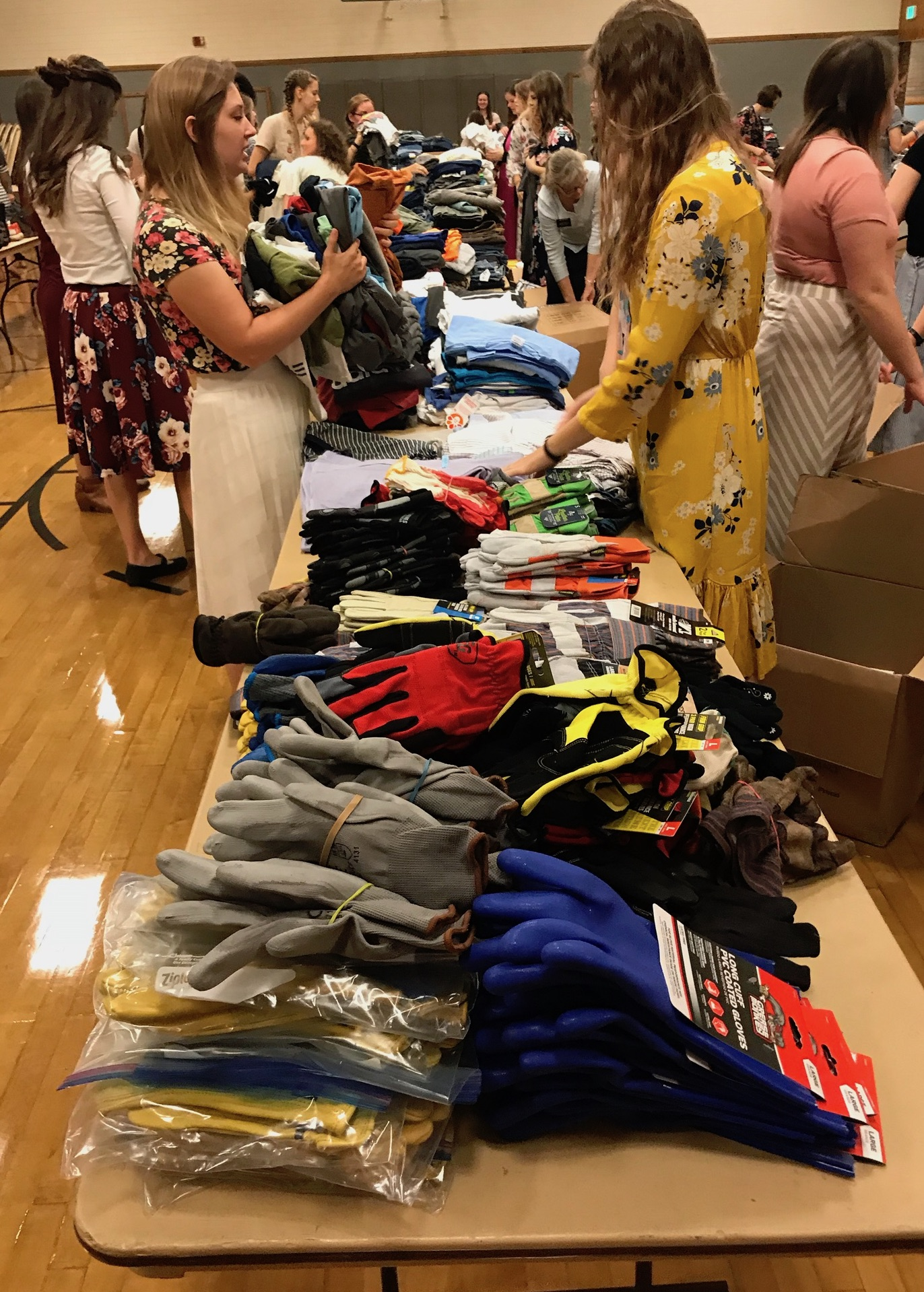 Sisters from the North Carolina Raleigh Mission sort through work clothes donated by members from the Oakton Virginia Stake.