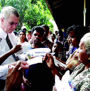 Bishop Richard C. Edgley, first counselor in the Presiding Bishopric, takes part in distribution of relief supplies i Sri Lanka to those made homeless by Dec. 26, 2004 tsunami. Accompanied by Elder John B. Dickson and elder Daryl H. Garn of the Seventy, Bishop Edgley and others traveled through the hardest hit areas of south Asia to determine the Church's response to those in need.