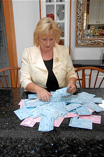 Renee Starr, of the South Hills Ward, Glendora California Stake, sits in her home surrounded by temple ordinance cards.