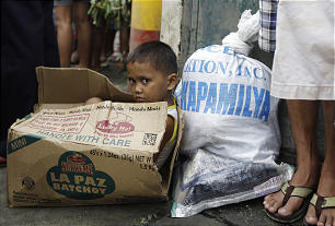 A Filipino boy sits inside an empty carton as he waits for his parents to receive relief goods in an area north of Manila.