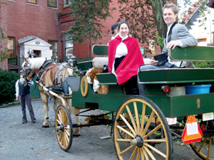 Nicole Benvie, portraying Vilate Young, and Fred Brown, portraying Brigham Young, arrive in horse-drawn carriage during the plaque dedication ceremony.