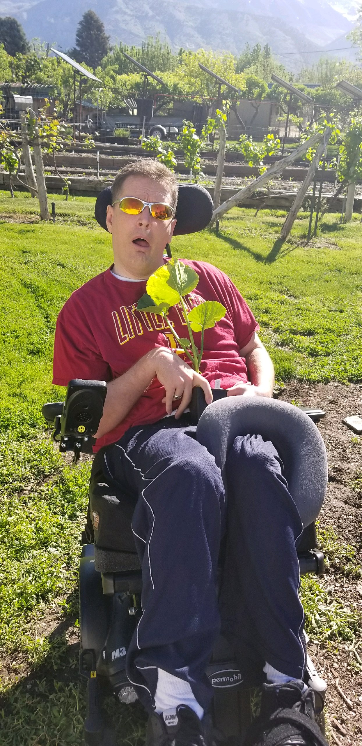 Orin Vooheis holds a pumpkin plant before planting in the garden. More than 20 years after being shot in the head on his mission, Voorheis is living a happy life surrounded by family and friends.