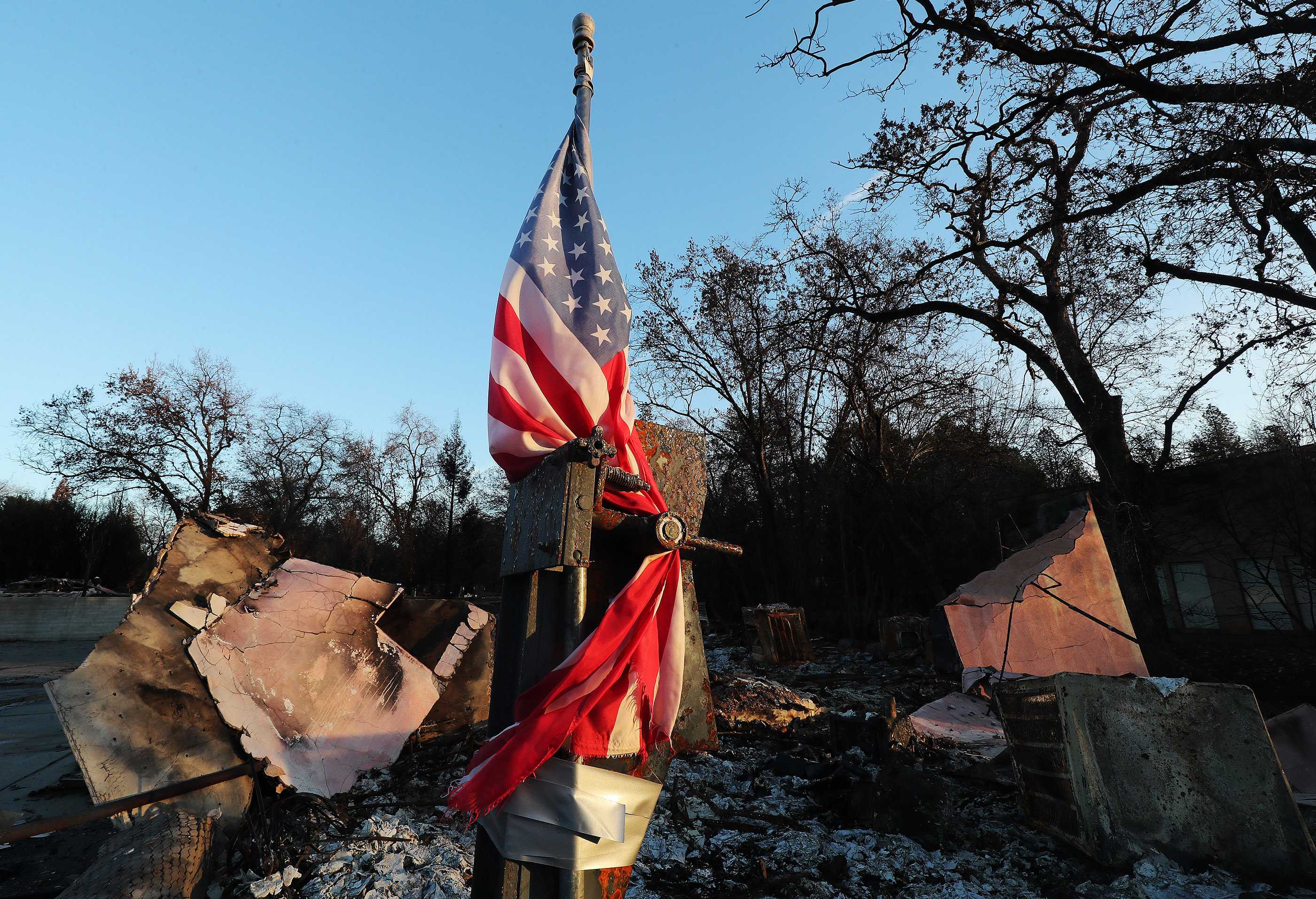 A flag flies over damage in Paradise, California, on Saturday, Jan. 12, 2019, two months after the Camp Fire destroyed more than 18,000 homes and businesses.