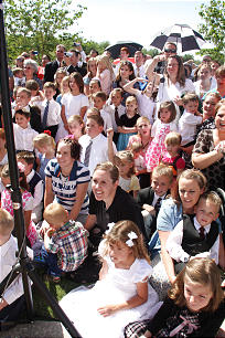 Children, youth and adults on The Gila Valley Arizona Temple grounds beam as they look toward President Monson.