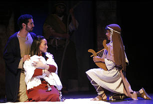 Joseph and Mary converse with a shepherd boy.