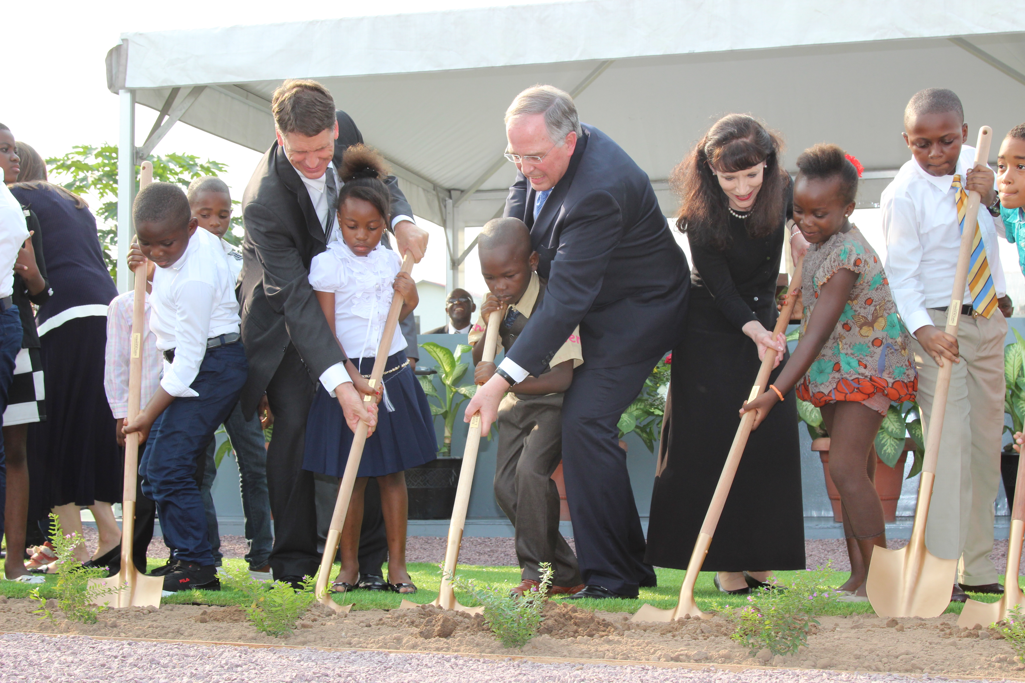 Elder Neil L. Andersen and his wife, Sister Kathy Andersen, and Africa Southeast Area president, Elder Carl B. Cook, help local children as they break ground for the Kinshasa Democratic Republic of the Congo Temple on Friday, February 12, 2016.