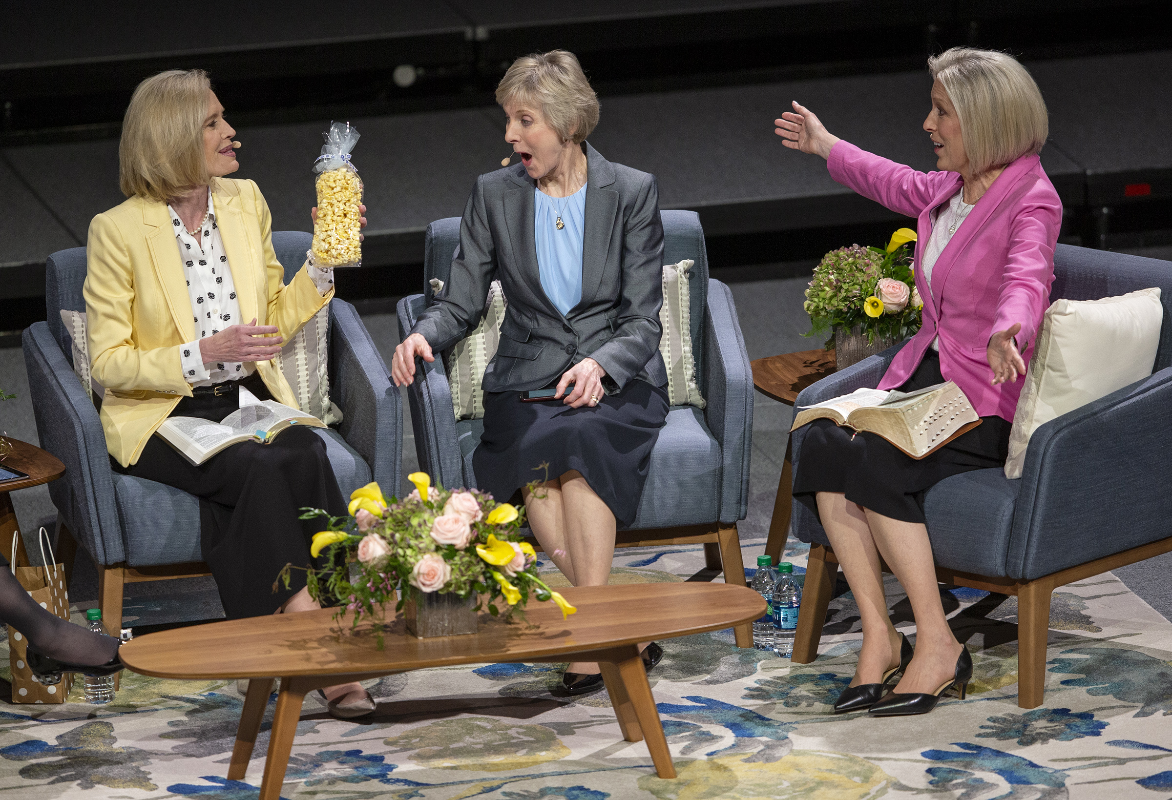 "Sister Bonnie H. Cordon, Young Women general president, left holds a bag of popcorn before giving it to Sister Joy D. Jones, Primary general president, right, who is joined in her reaction by Sister Jean B. Bingham, Relief Society general president, during a ""Sister to Sister"" event at Women's Conference at BYU's Marriott Center in Provo, Utah, on Friday, May 3, 2019."