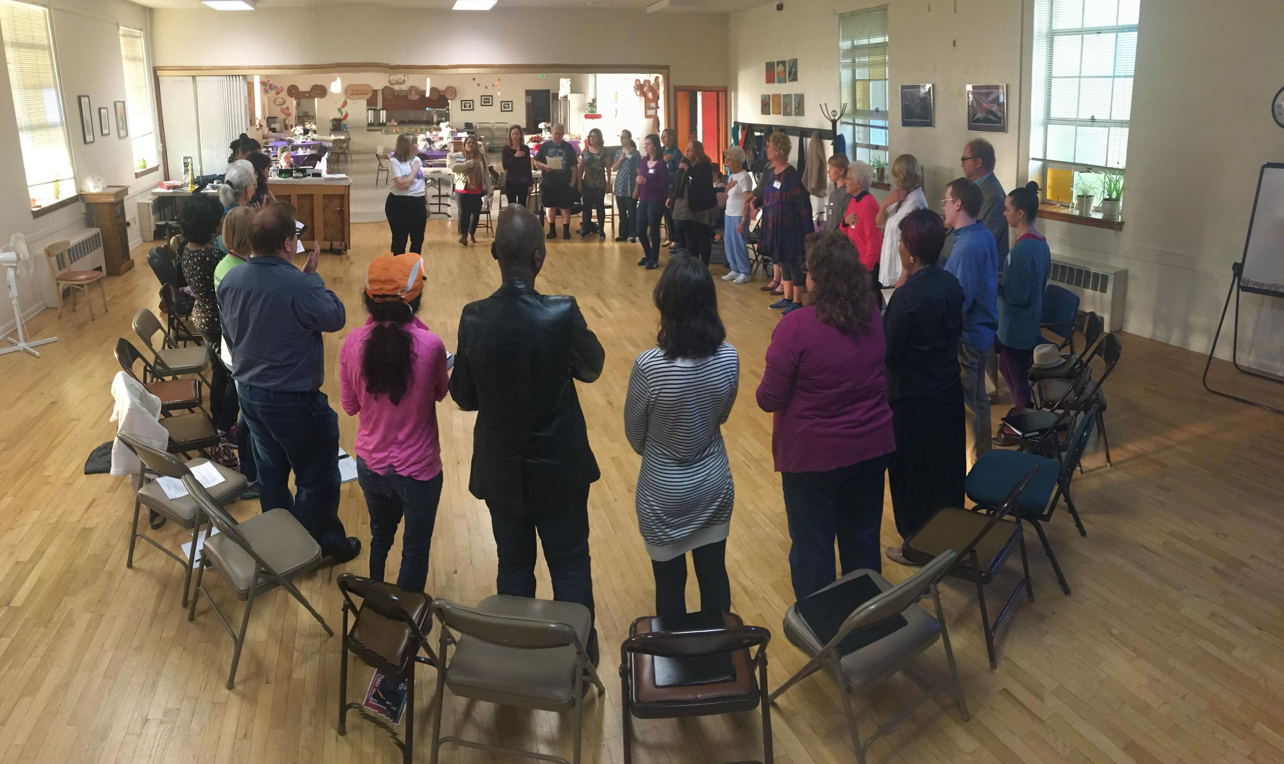 The Tacoma Refugee Choir stands in a circle during one of their rehearsals.
