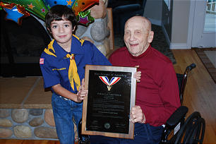 LaGrand Nielsen poses for a photo with neighbor, Cub Scout Cian Hildebrandt. Brother Nielsen displays an award honoring him as a Distinguished Eagle Scout.