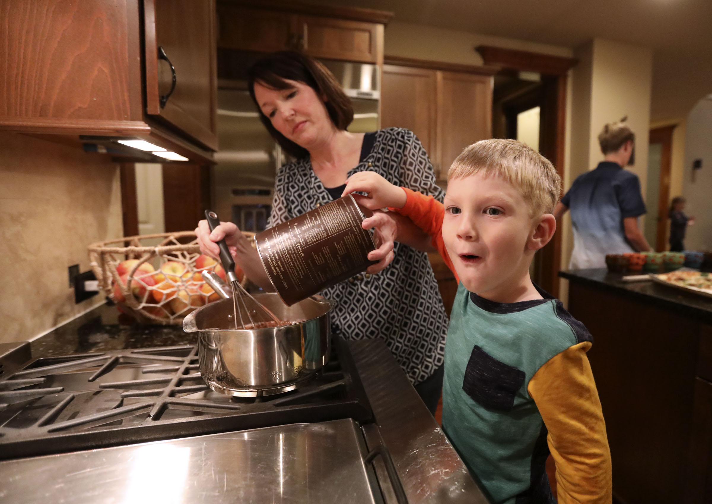 Alexis Allen helps her son Daniel Allen make hot chocolate at home in Renton, Wash., on Friday, Sept. 14, 2018.