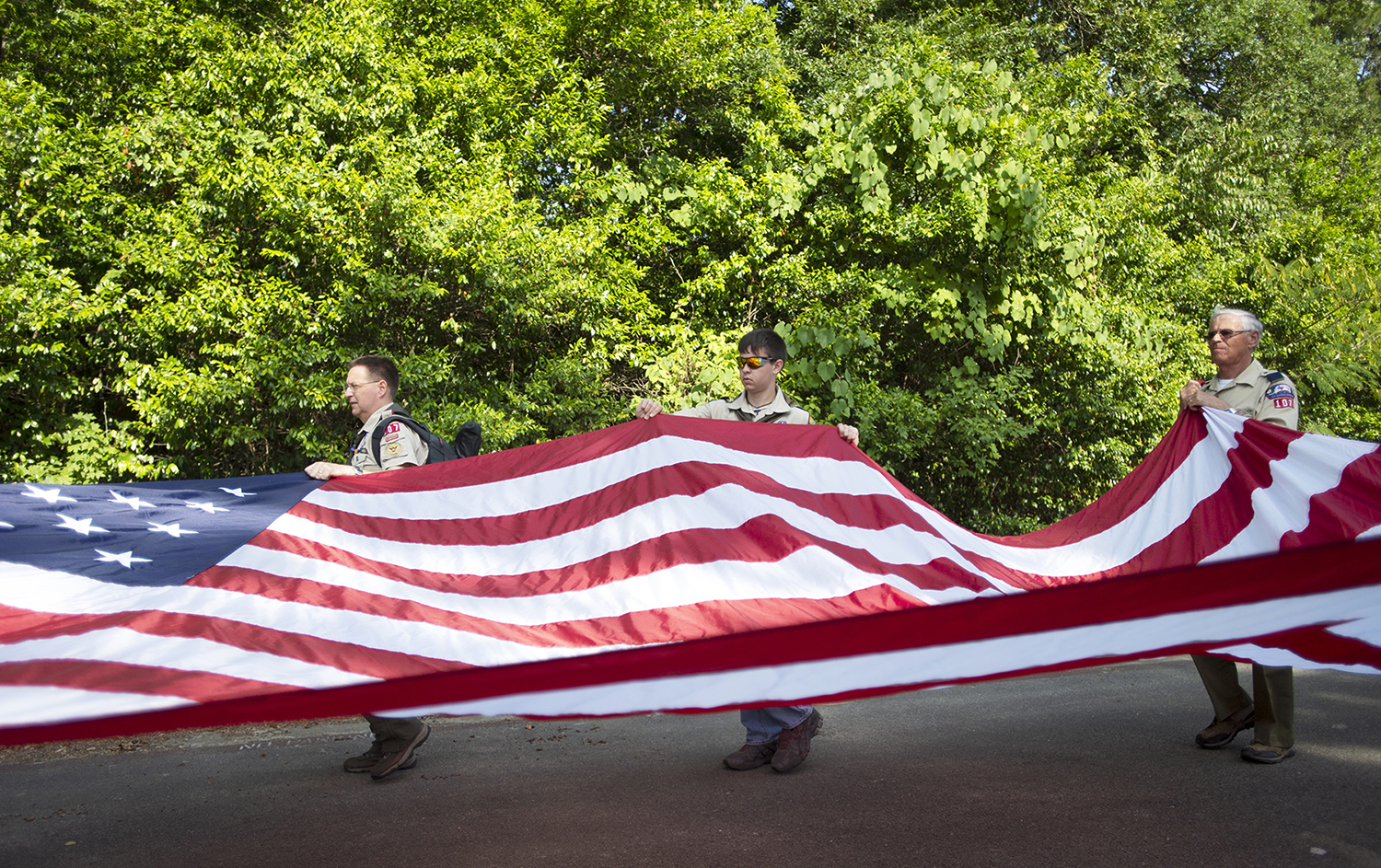 Boy Scout Troop 107 members Scott and Billy Ishmael, left and center, and Ray Stoner, right, carry a large American flag in the Brooks-Quinn Jones Elementary School Independence Day Parade on Tuesday, July 3, 2018, in Nacogdoches, Texas.