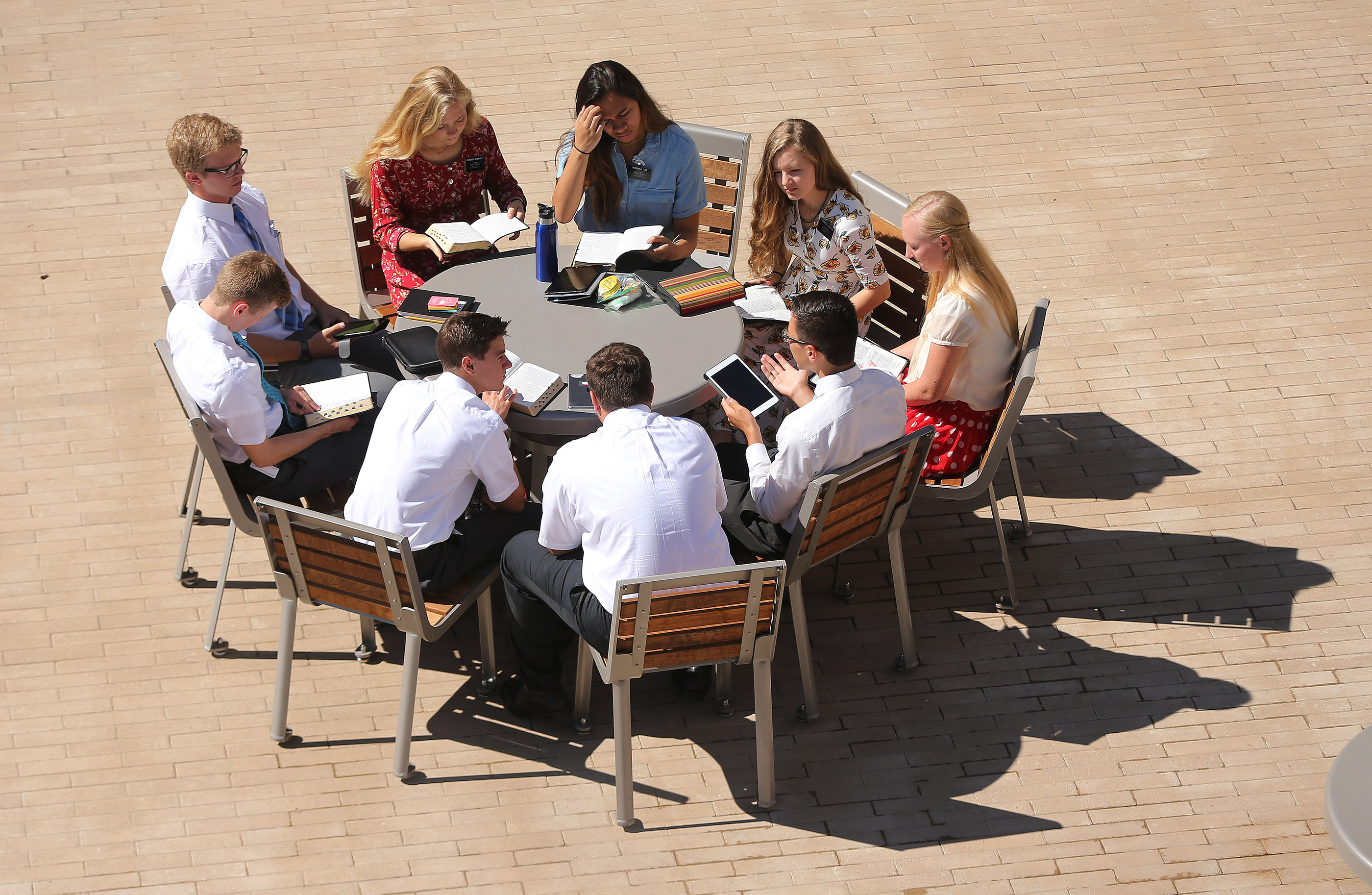 Missionaries study and converse at a table outside in an open-space setting at the Provo Missionary Training Center in Provo on Wednesday, July 26, 2017.