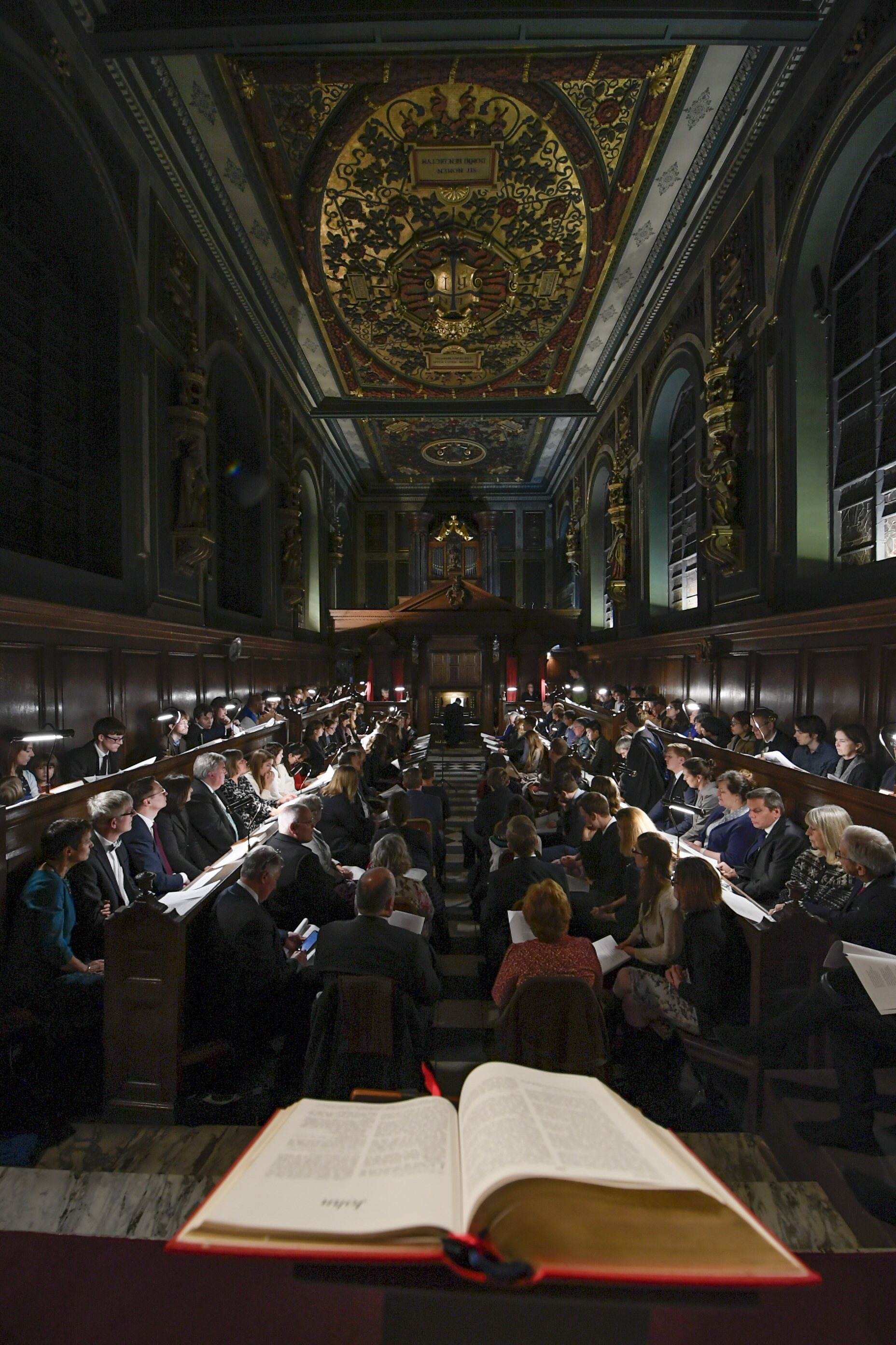 """The congregation listens to a Biblical selection about Jesus Christ during the traditional Church of England """"Nine Lessons and Carols"""" service at the Pembroke College Chapel in Oxford, England, on Sunday, Nov. 25, 2018."""