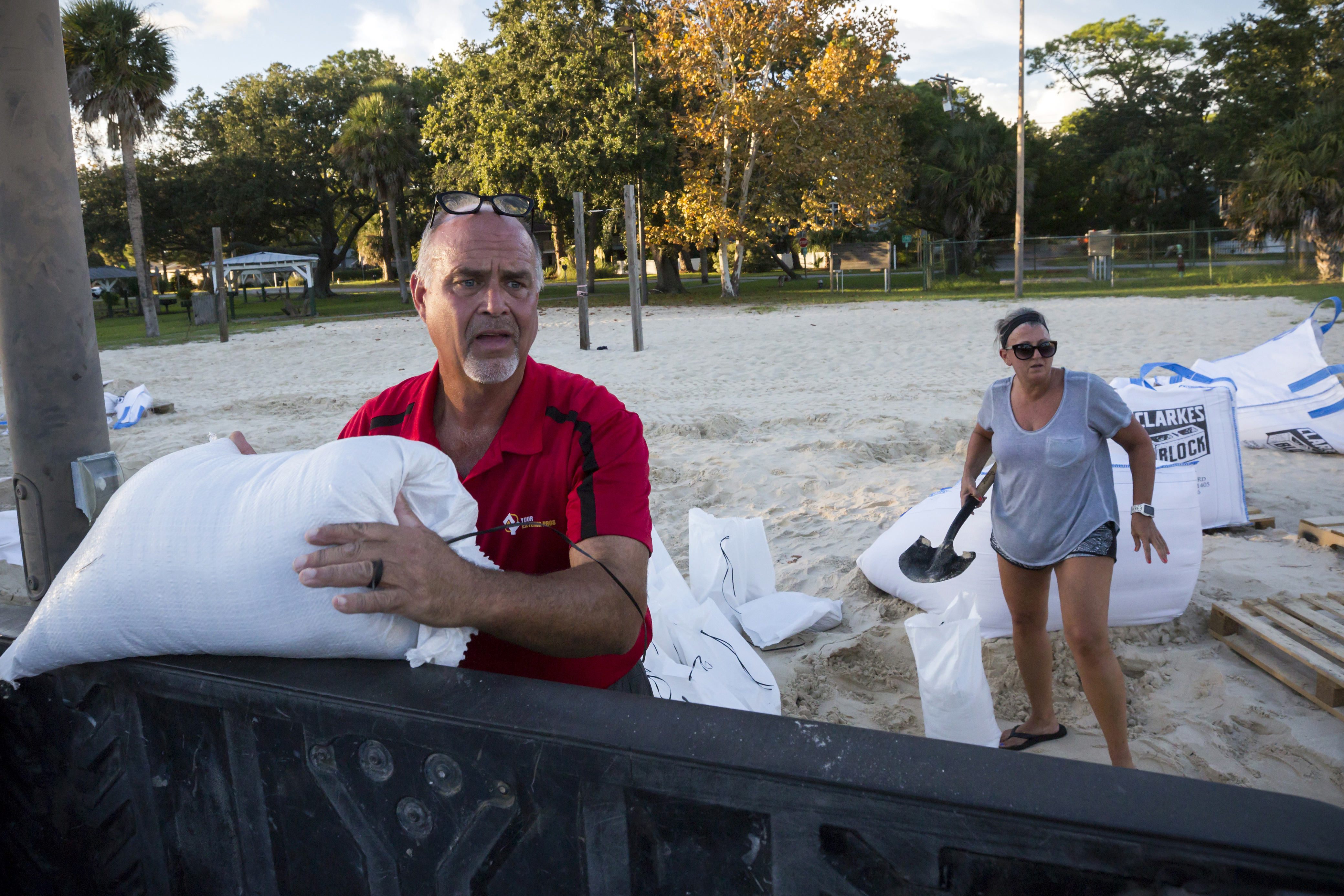 Tybee Island residents Sib McLellan, left, and his wife, Lisa McLellan, load sandbags into the back of their truck while preparing for Hurricane Florence, Wednesday, Sept., 12, 2018, on Tybee Island, Ga.