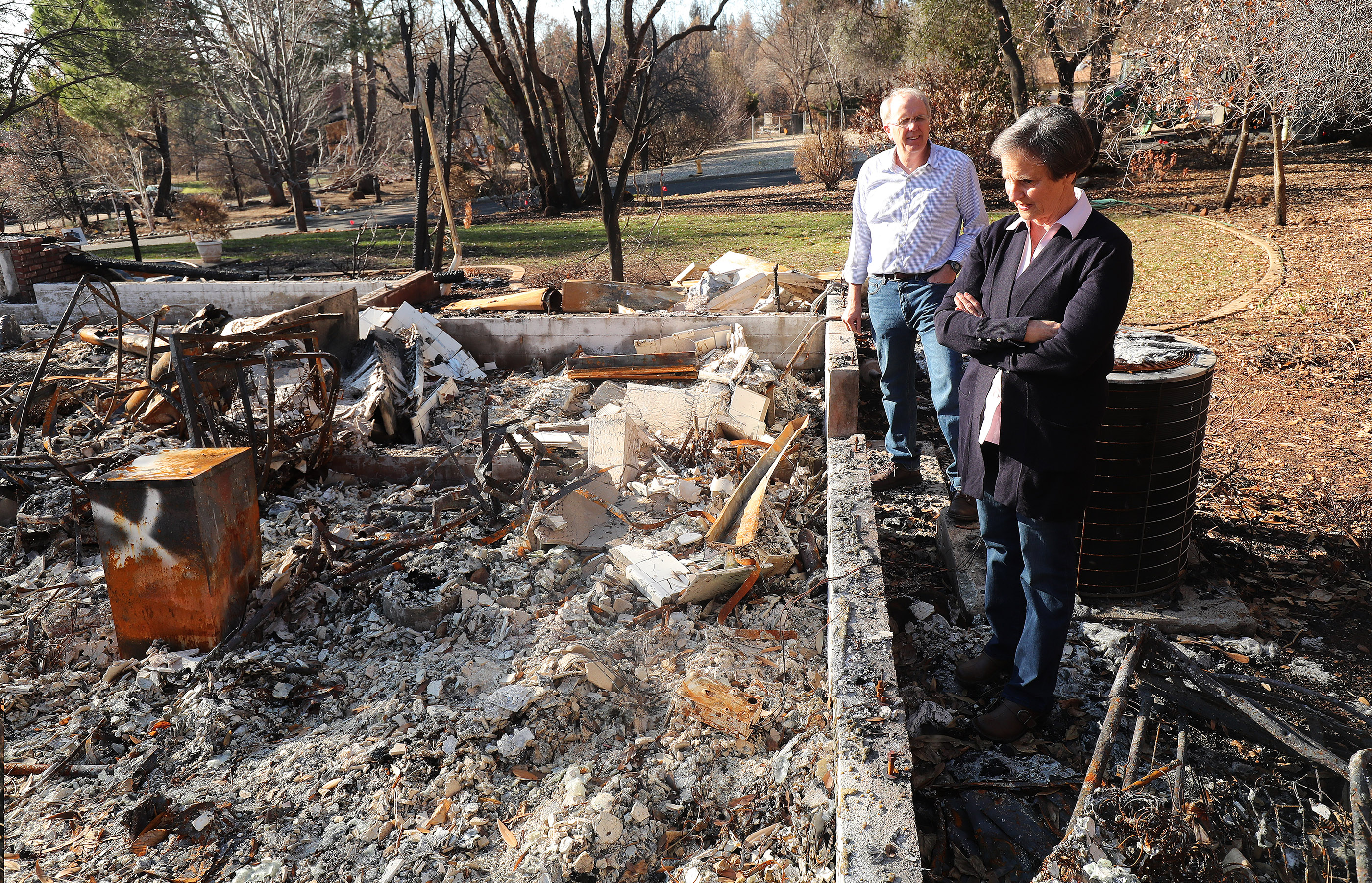 Rick and Kathie Turner look over their destroyed home in Paradise, California, on Saturday, Jan. 12, 2019, two months after the Camp Fire destroyed more than 18,000 homes and businesses.