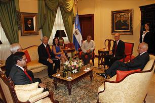 Seated clockwise, El Salvador's President Mauricio Funes, next to flag, President Henry B. Eyring, Elders D. Todd Christofferson, Carlos Rivas, William R. Walker, Enrique R. Falabella, El Salvador's first lady Vanda Pignato.