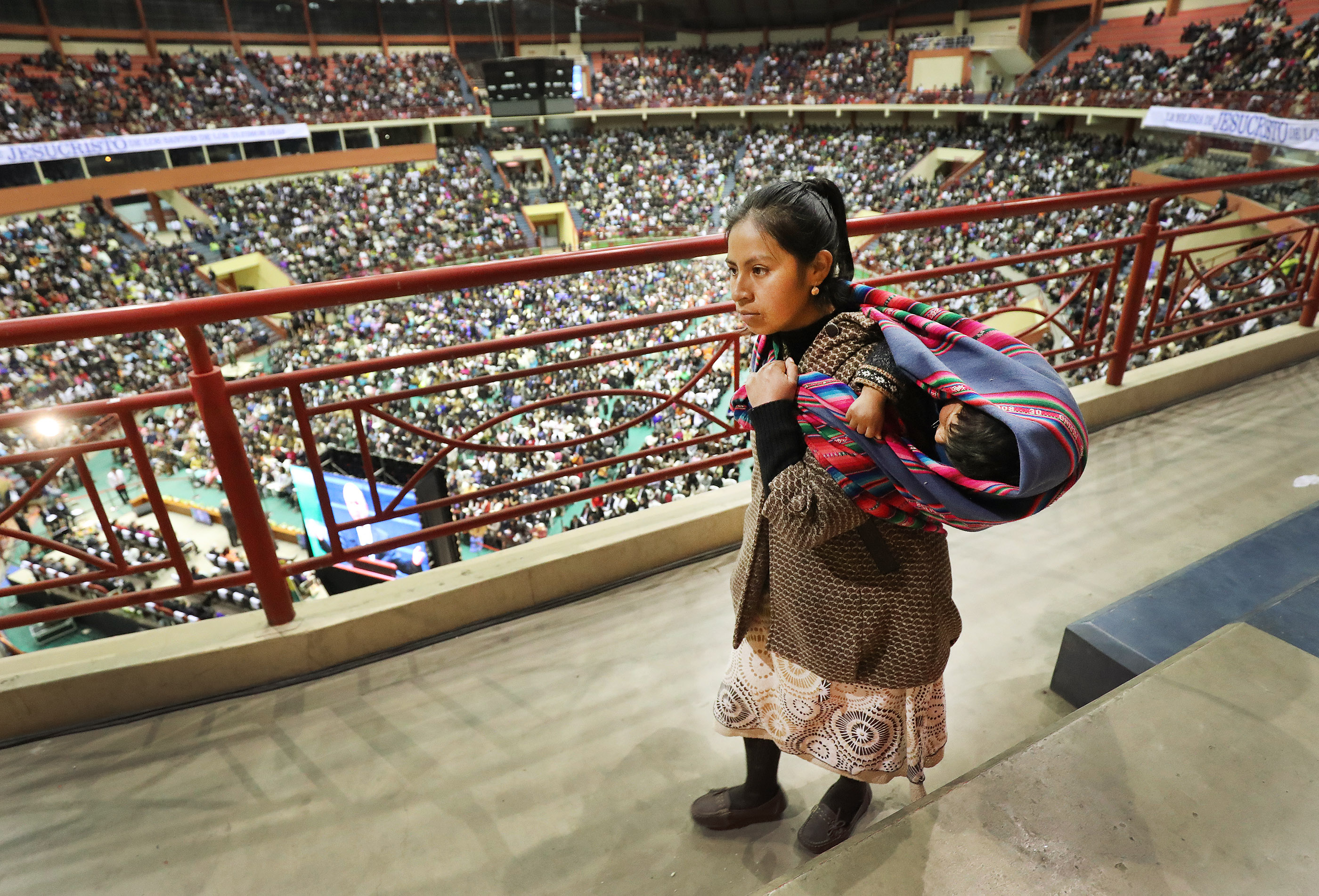 A woman carries a child as President Russell M. Nelson of The Church of Jesus Christ of Latter-day Saints speaks in La Paz, Bolivia on Oct. 21, 2018.