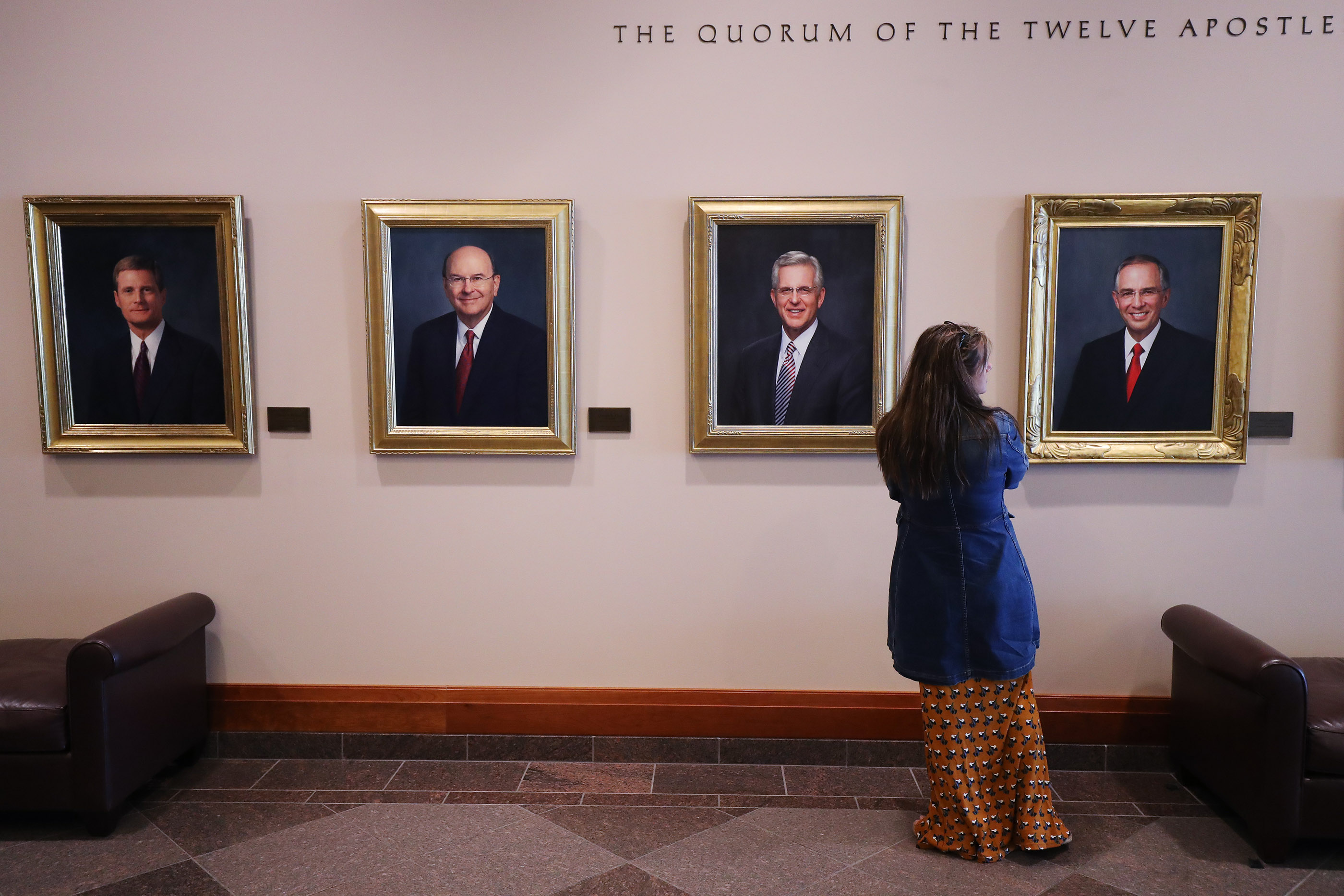 A conference attendee looks over portraits of the Quorum of the Twelve Apostles during the 188th Semiannual General Conference of The Church of Jesus Christ of Latter-day Saints in Salt Lake City on Sunday, Oct. 7, 2018.