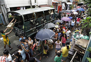 Residents queue for relief goods in a hard-hit residential area in suburban Quezon City, north of Manila.