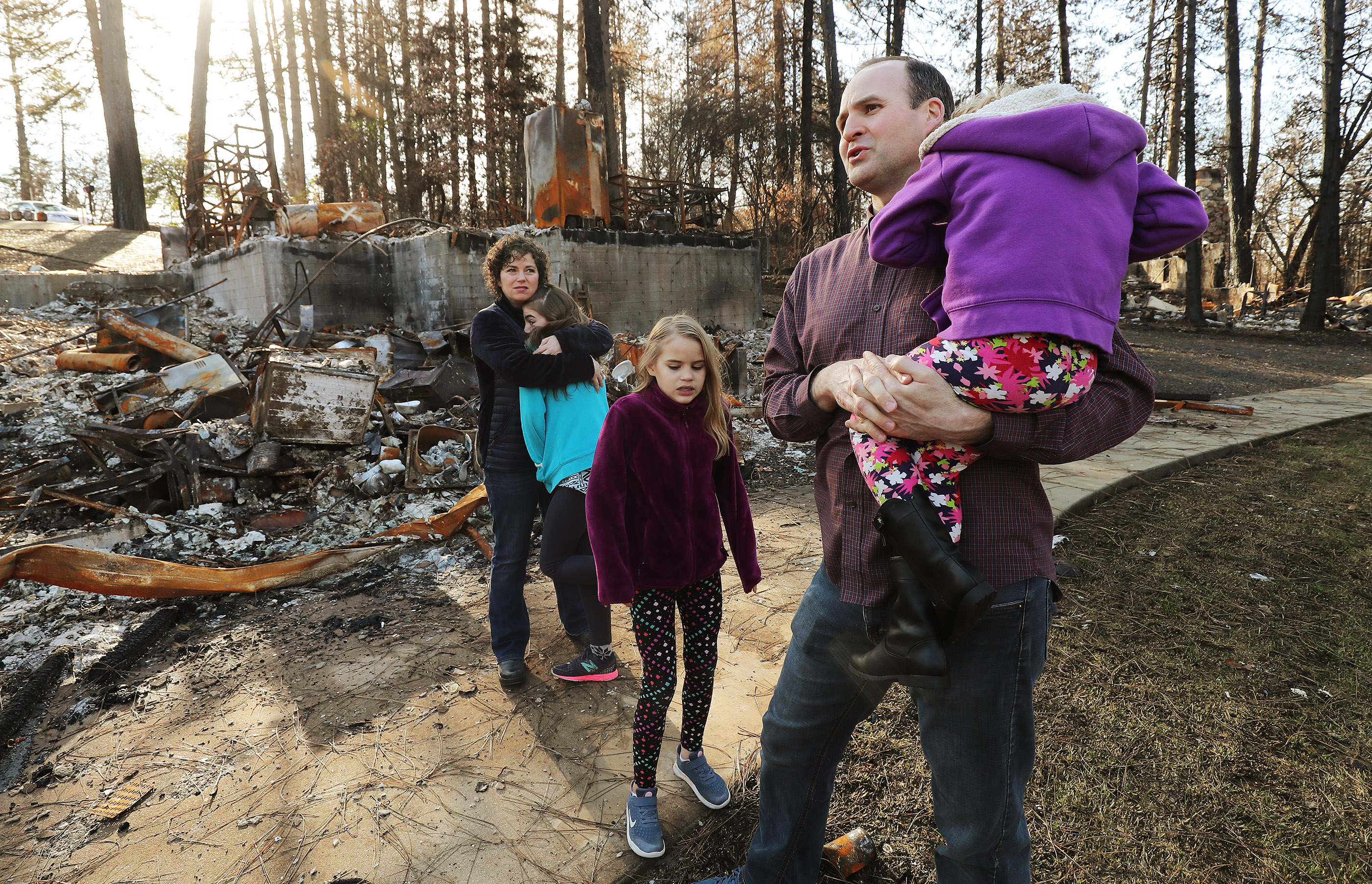 Jeremy and Brynn Chatfield and their children McKell, Aylee and DeLynn survey their destroyed home in Paradise, California, on Saturday, Jan. 12, 2019, two months after the Camp Fire destroyed more than 18,000 homes and businesses.