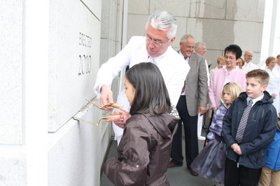 President Dieter F. Uchtdorf, second counselor in the First Presidency, assist Grace DeFeo, 9, as she puts mortar in the Vancouver temple cornerstone.