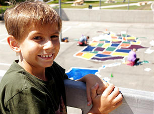 Chase Hales poses in front of a restored map of the United States at Marblehead Elementary in San Clemente, Calif. The map was part of service initiative, led by the Hales family, to express gratitude for the life of their son, a tumor survivor, and help others celebrate the gift of life.