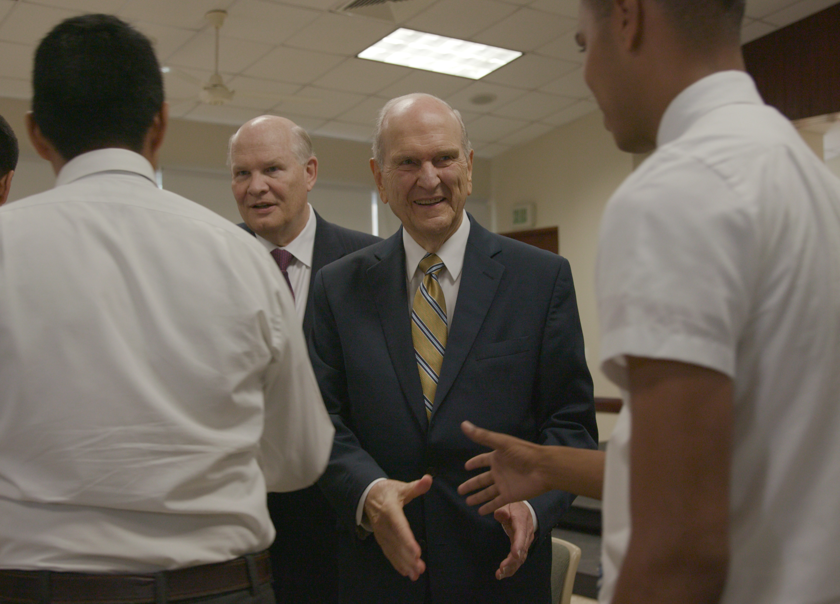 President Russell M. Nelson, right, and Elder Dale G. Renlund shake hands with missionaries at a Sept. 1, 2018, missionary meeting in Santo Domingo, Dominican Republic.