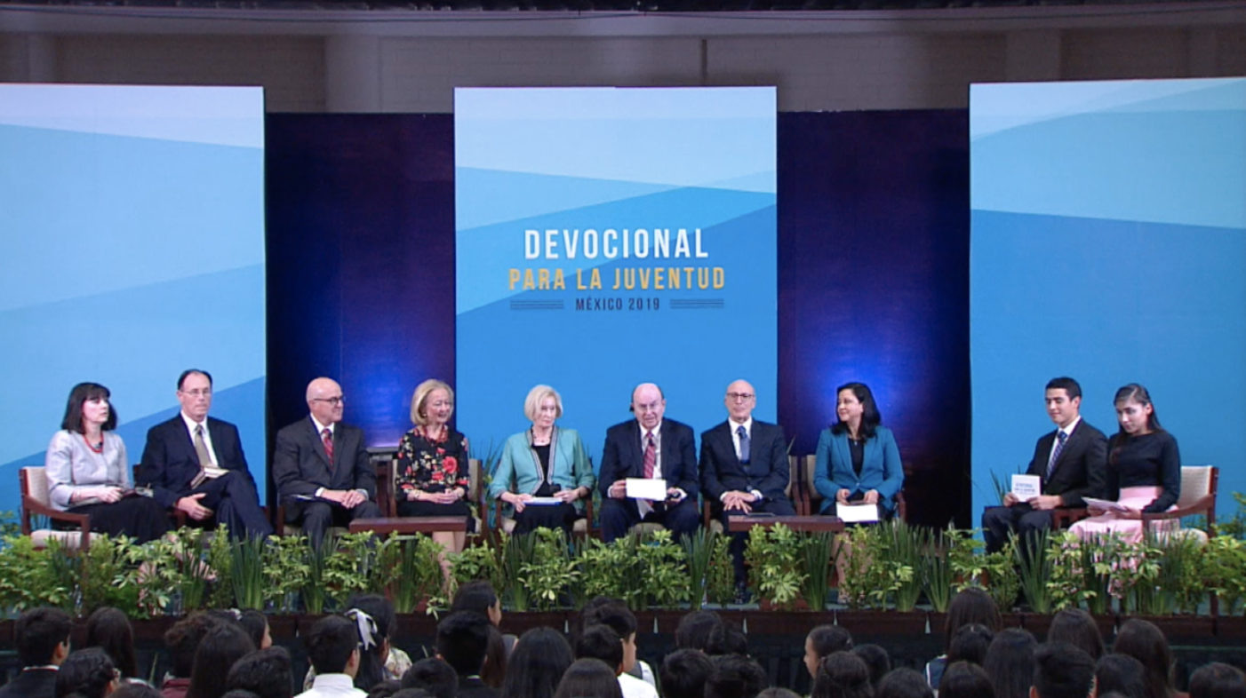 Church leaders — including Elder Quentin L. Cook and Sister Mary Cook, center; Elder L. Whitney Clayton and Sister Kathy Clayton, second couple from left; Bishop W. Christopher Waddell and Sister Carol Waddell, left; and Elder Arnulfo Valenzuela and Sister Silvia Valenzuela, right of the Cooks — participate in a youth devotional in Mexico City on Feb. 8, 2019. The leaders and their wives answered questions from the youth, with the event hosted by two youth, far right, from two Mexico City stakes — Karim Noffal Cabanillas, a priest in the Tacubaya stake, and Pahoran Parra Cruz, a Laurel from the Chapultepec stake.
