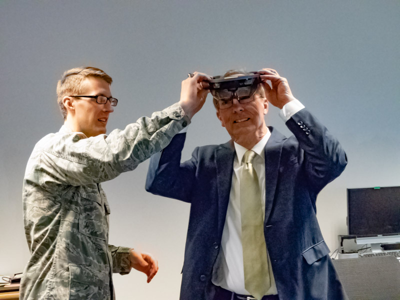 Connor Crandall, LDS graduating senior, assists Brother Tad R. Callister with the Microsoft HoloLens which displays the mission planning software that is the basis for his capstone project.