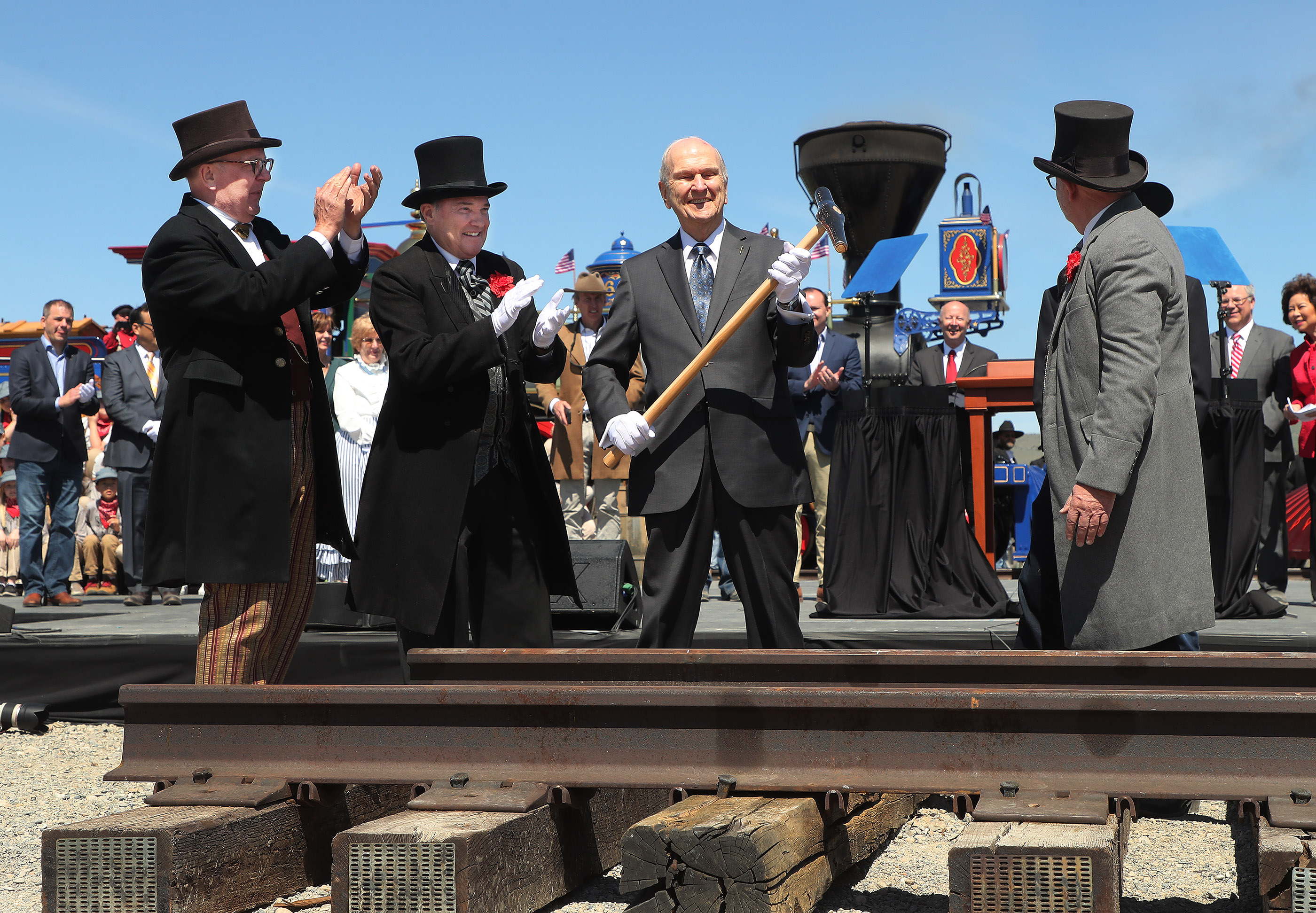 President Russell M. Nelson of The Church of Jesus Christ of Latter-day Saints, center, hoists his hammer after driving a golden spike during the 150th anniversary celebration of the transcontinental railroad at the Golden Spike National Historical Park at Promontory Summit on Friday, May 10, 2019.