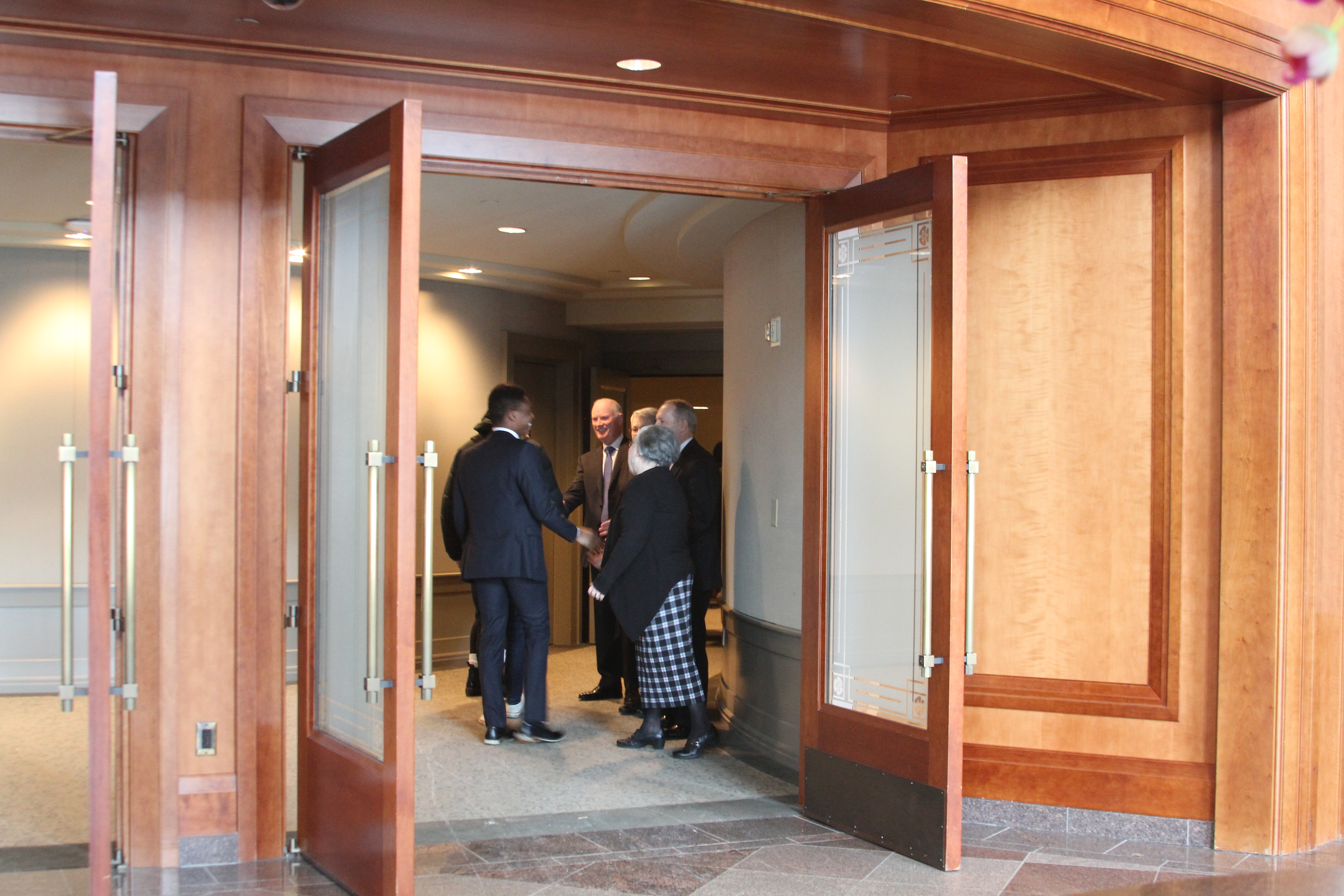 Elder Kim B. Clark, Sister Sue Clark, LDS Business College President Bruce C. Kusch and Sister Alynda Kusch greet LDS Business College students as they enter the Conference Center Theater for a devotional on Feb. 19, 2019.