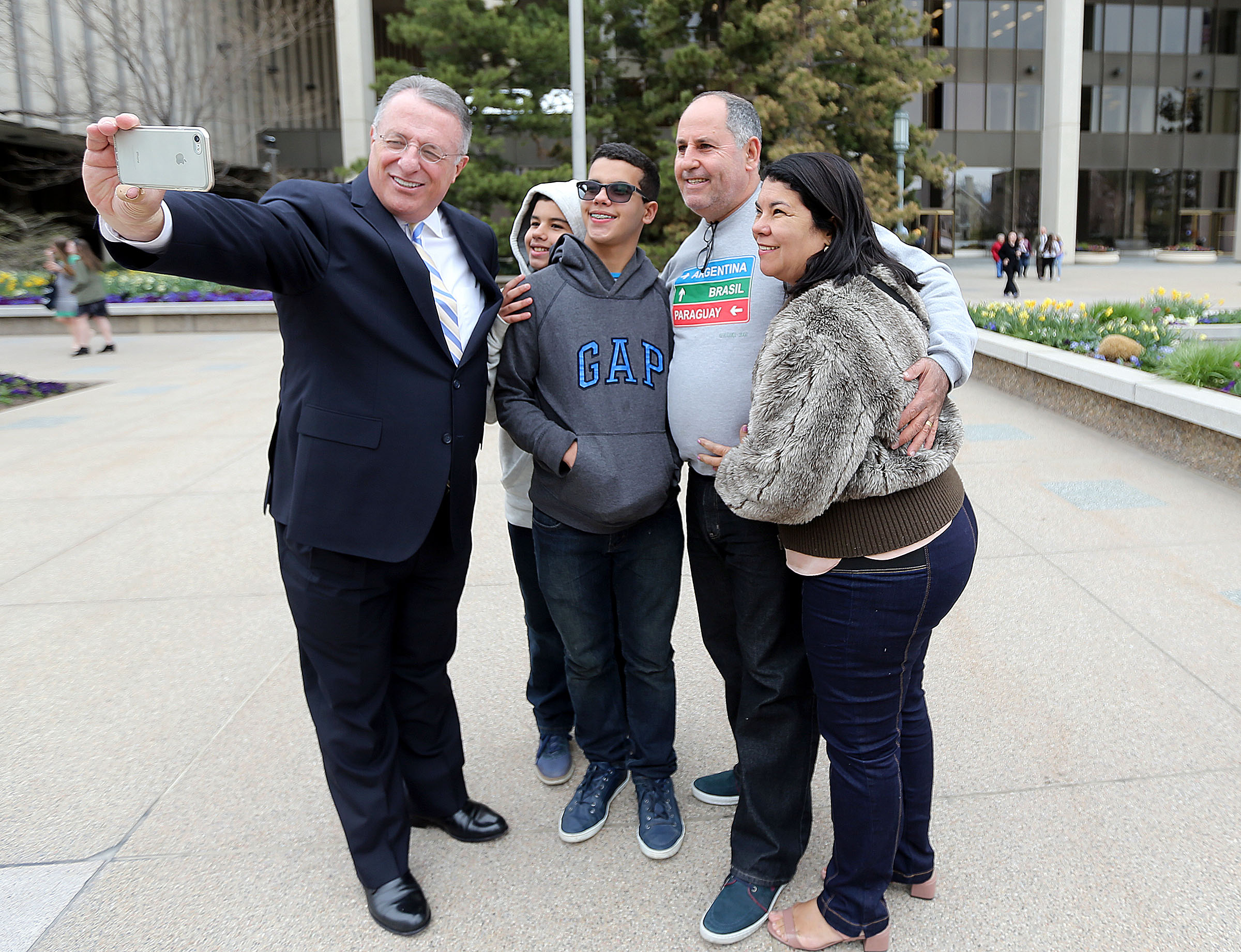 Elder Ulisses Soares takes a selfie with Marcell Pragana, Matheus Pragana, Marcus Pragana and Maria Pragana outside of the Church Administration Building in Salt Lake City on Wednesday, April 4, 2018.