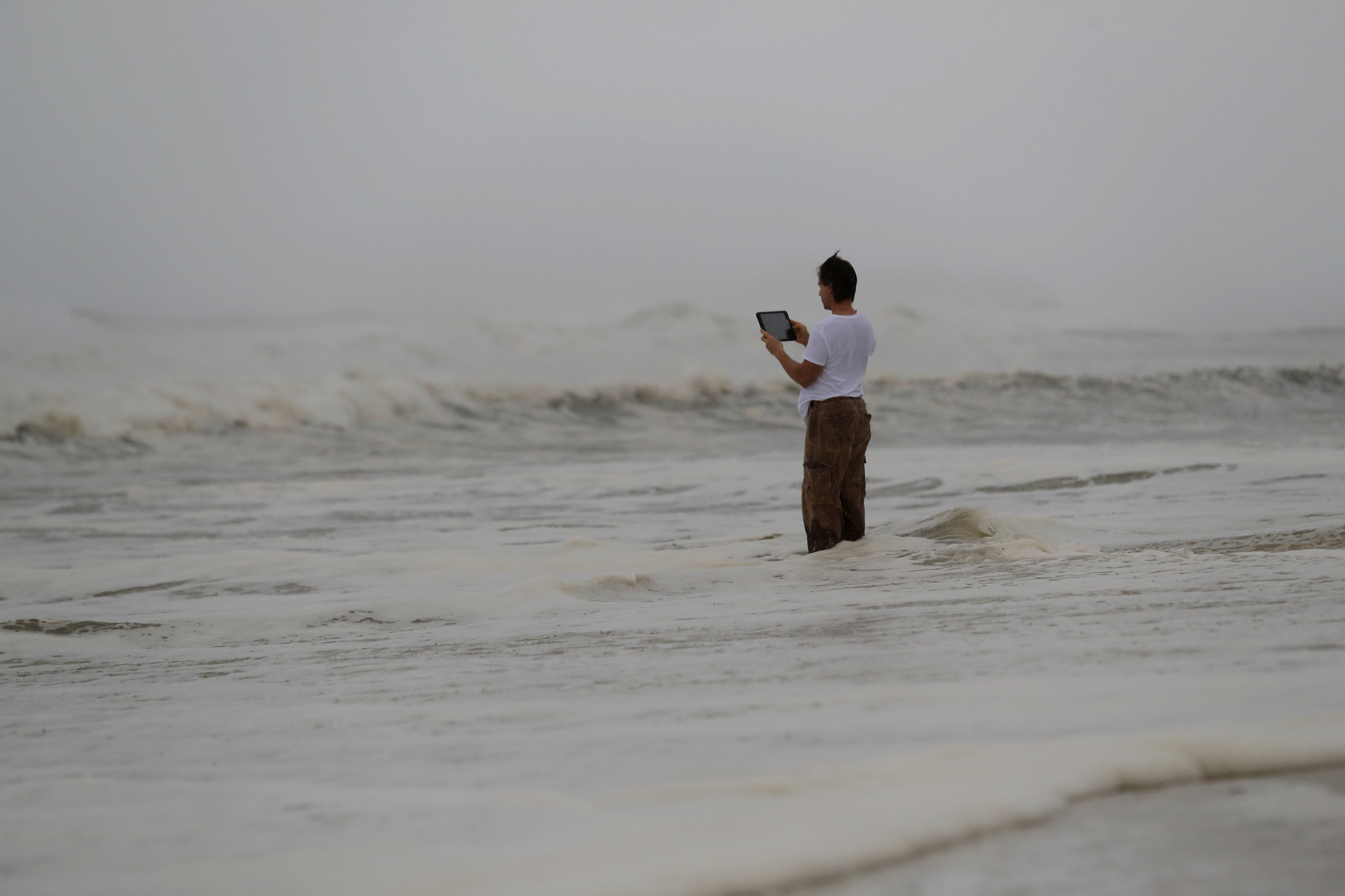 Peter Malave records the surf from encroaching Hurricane Michael, which is expected to make landfall Wednesday, Oct. 10, 2018, in Panama City Beach, Fla. The hurricane center says Michael will be the first Category 4 hurricane to make landfall on the Florida Panhandle. (AP Photo/Gerald Herbert)