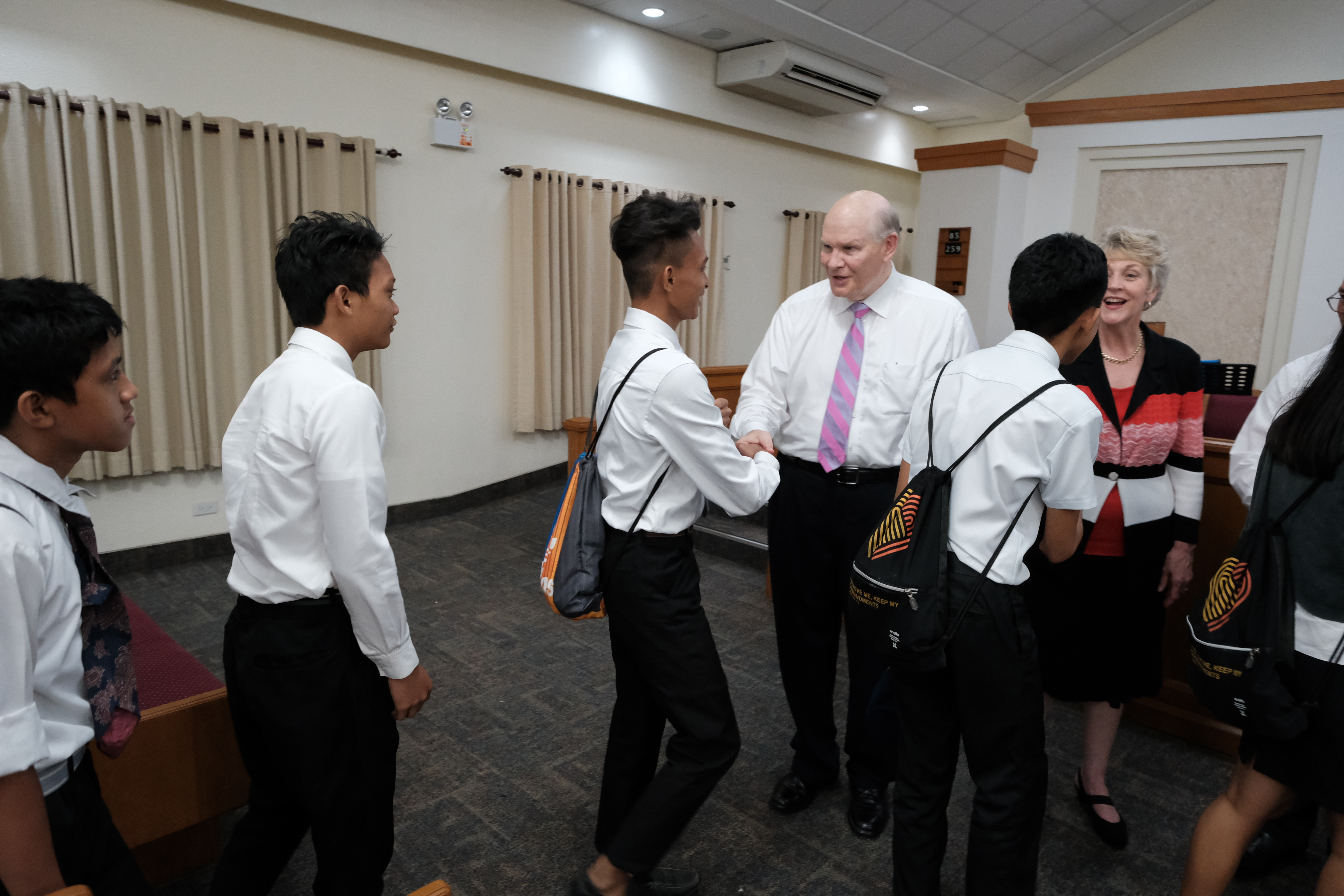 Elder Dale G. Renlund and Sister Ruth Renlund greet youth of the Talisay Philippines Stake.