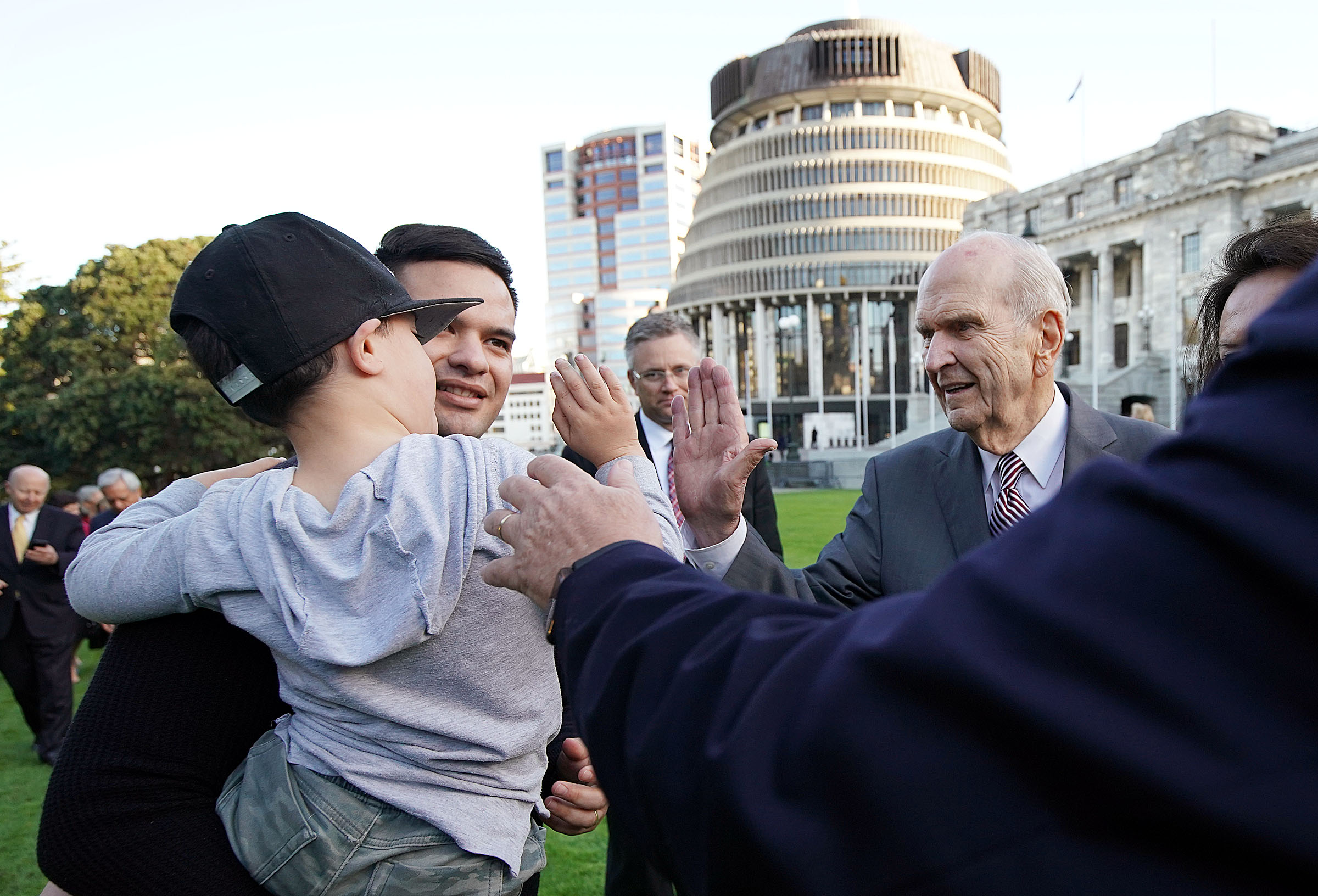 President Russell M. Nelson of The Church of Jesus Christ of Latter-day Saints, right, greets Quentin Daniels and his son Archer Daniels after meeting with New Zealand Prime Minister Jacinda Ardern in Wellington on Monday, May 20, 2019.