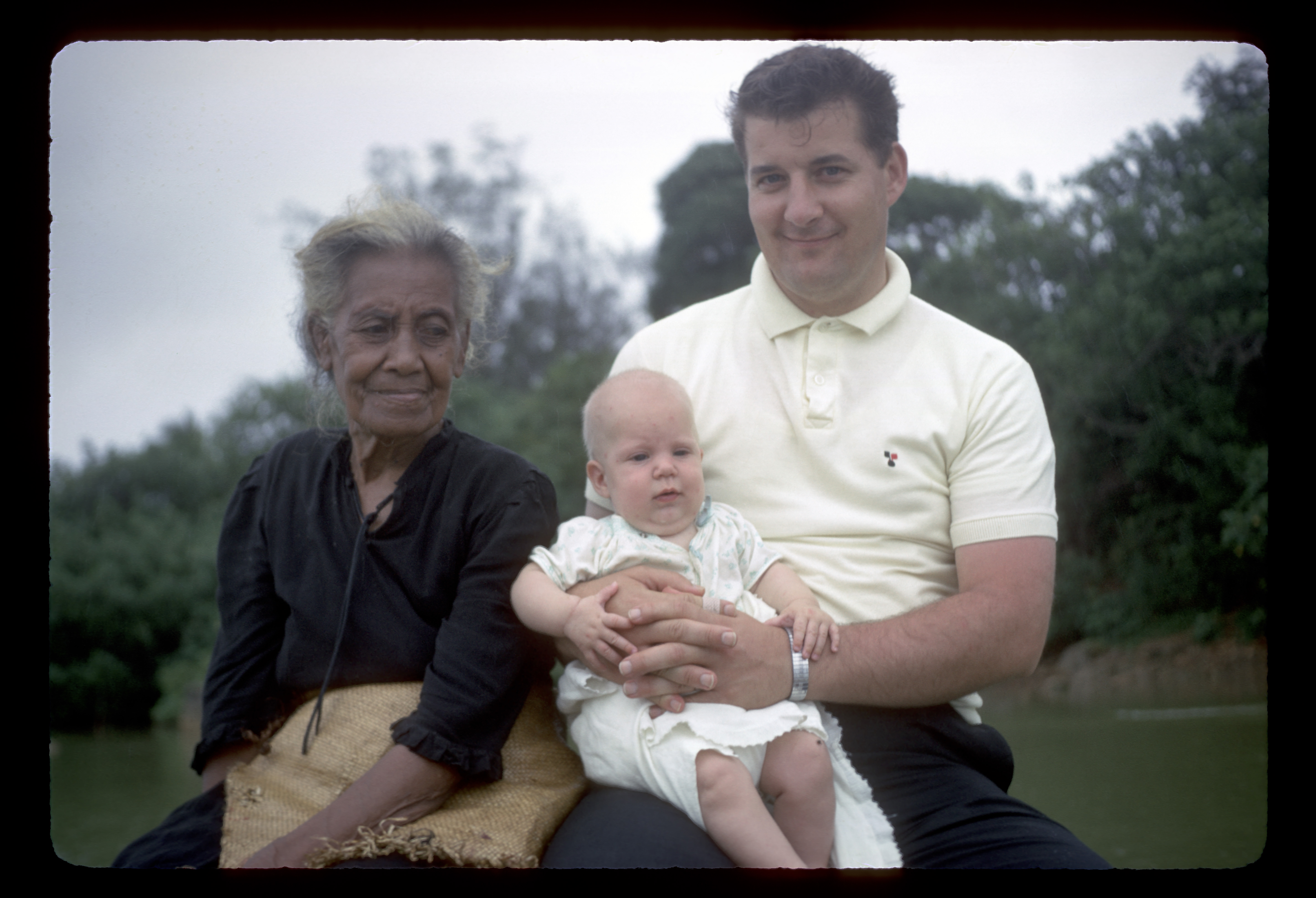 Elder John Groberg, holds baby Gayle while sitting with a Tongan member during a boat trip to some of the little Tongan islands in September 1966.