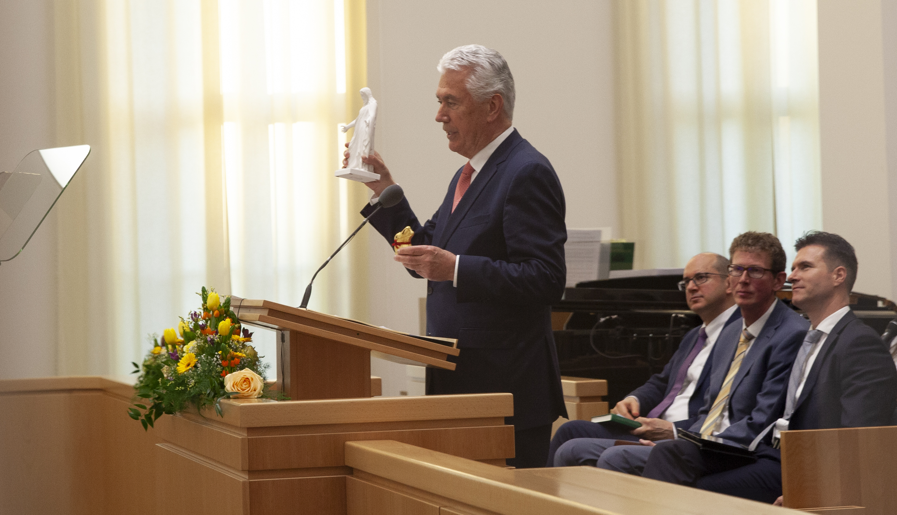 Elder Dieter F. Uchtdorf of the Quorum of the Twelve Apostles, holds a Lindt chocolate bunny in one hand and a small Christus statue in the other as he speaks of the importance of Easter during the April 20, 2019, regional Face to Face broadcast with German-speaking Latter-day Saints in Europe. The broadcast originated in Frankfurt, Germany.