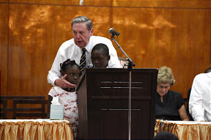 Elder Holland stands with two children during a meeting in Sierra Leone on Feb 18, 2012.