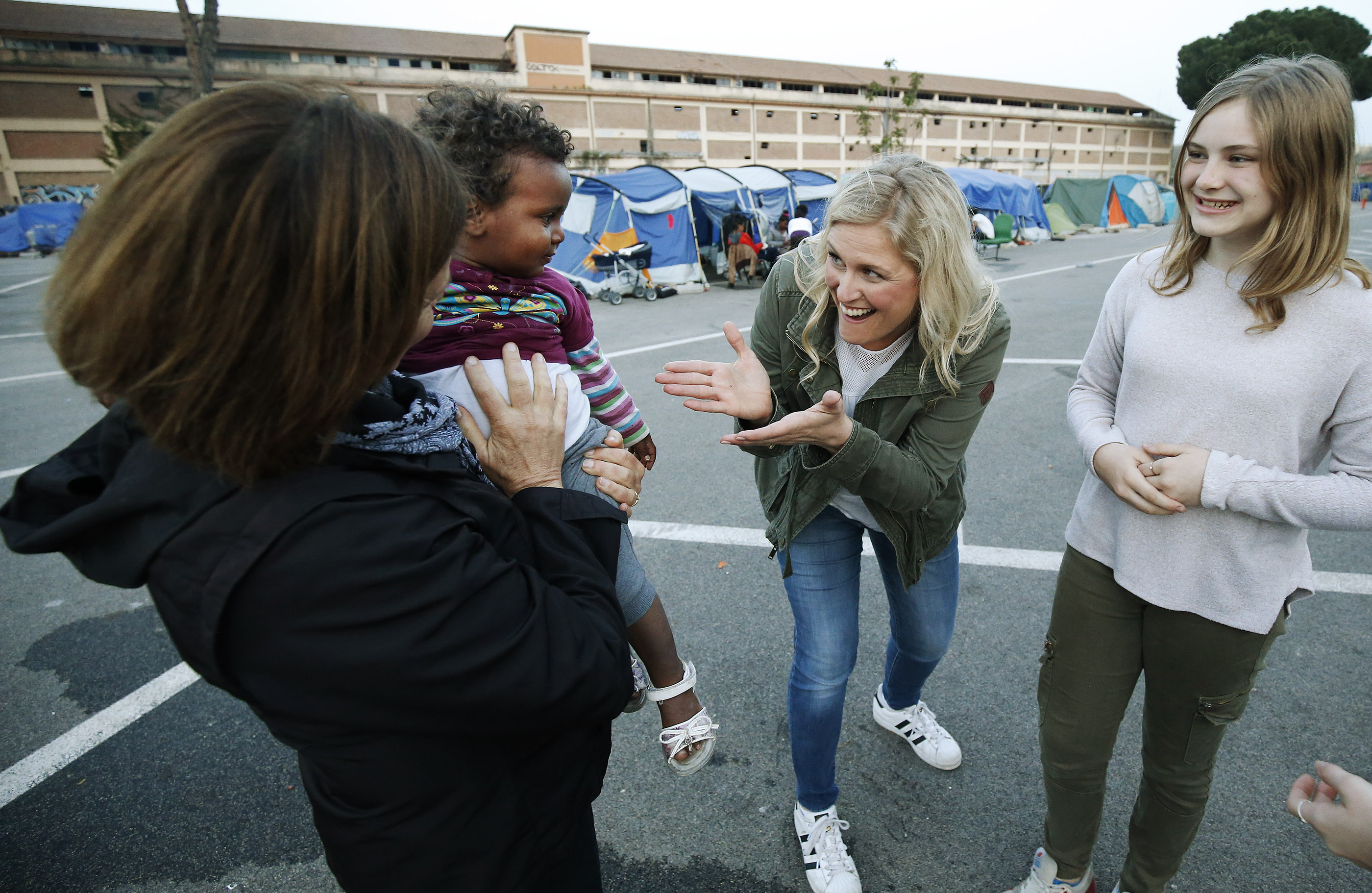 LDS Charities missionary Anita Herway, left, and LDS Church members Ariane and Kate Woods play with a refugee child at Baobob refugee camp in Rome, Italy, on Monday, April 16, 2018. LDS Charities contributes volunteers, dining tents, and money to the organization.
