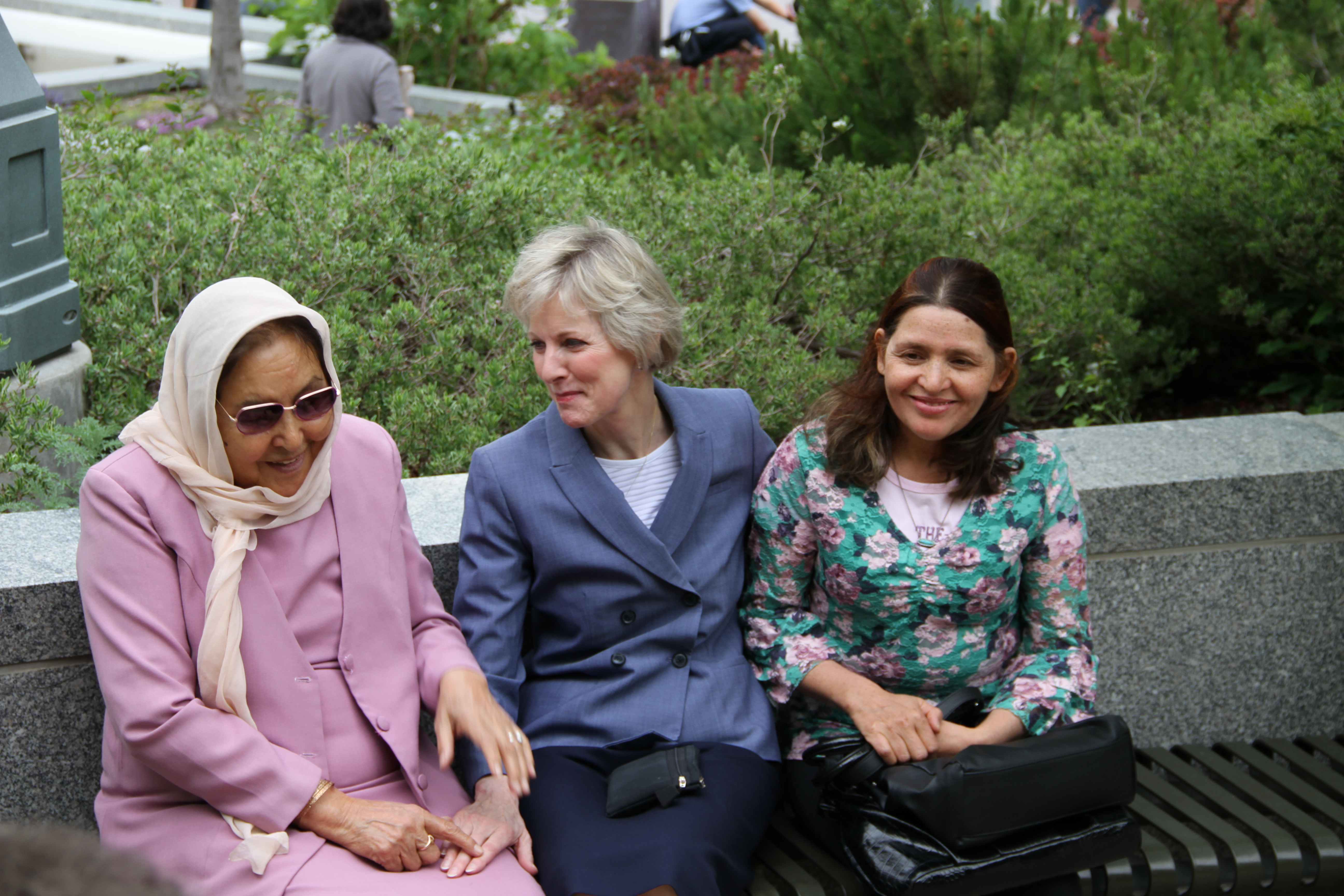Sister Jean B. Bingham sits outside on Temple Square with Asifa Nadir, left, and Nadira Nadir, right, while being filmed by Lucian Perkins from USA for UNHCR on May 16, 2019. Sister Bingham has known the Nadir family, refugees from Afghanistan for nearly 15 years.