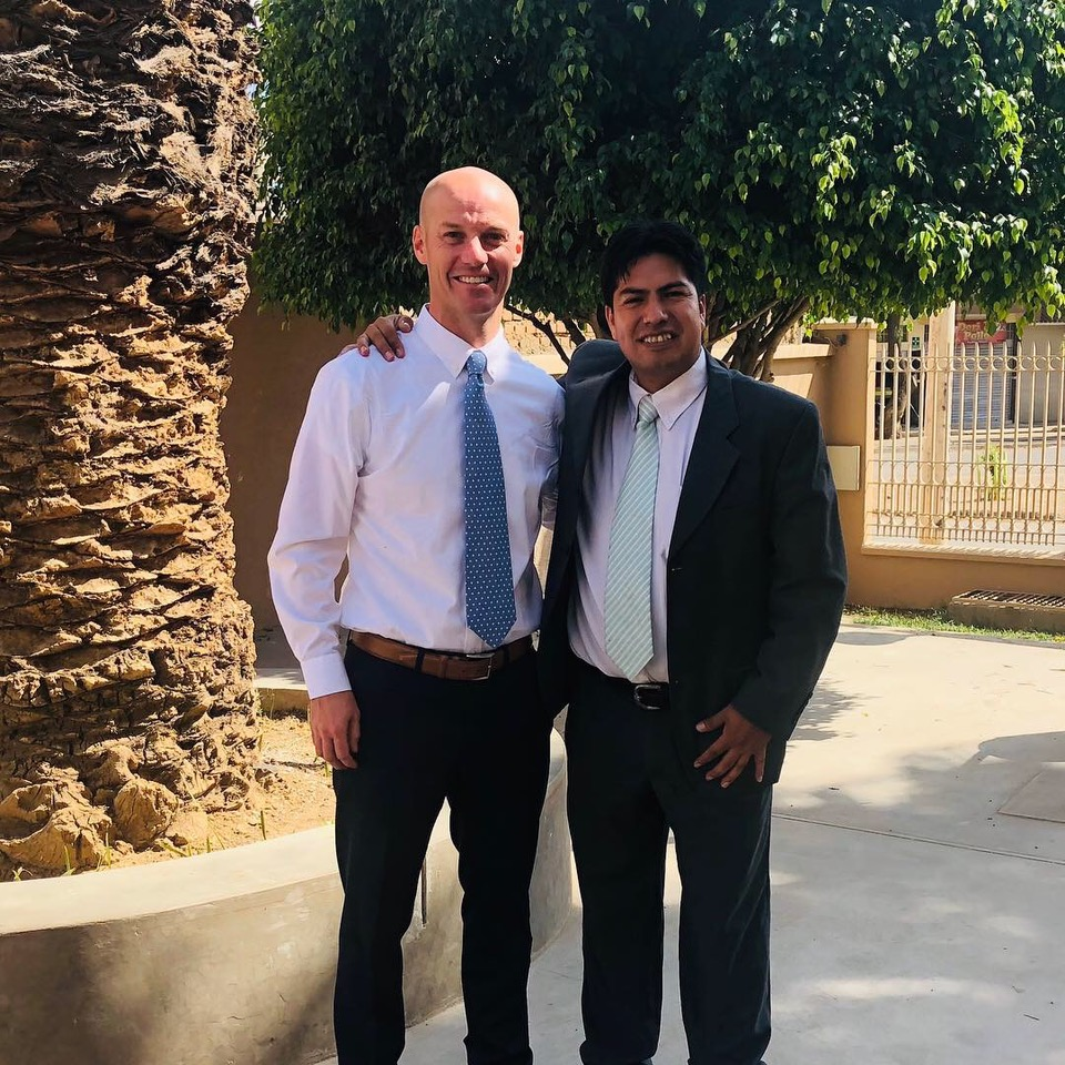 Scott Mortensen (left) and and Gonzalo Cadiz by the same palm tree, now fully grown, outside the Church where Mortensen baptized Cadiz nearly 20 years ago.