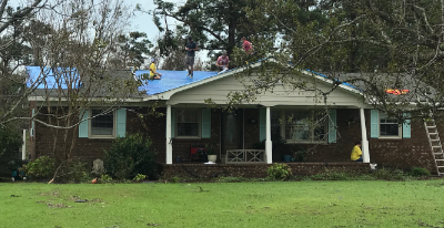 Members in yellow Helping Hands T-shirts patch up a damaged roof and clear away debris outside a Harkers Island, North Carolina, home damaged by Hurricane Florence. The service was being done on Sunday, Sept. 16, 2018.