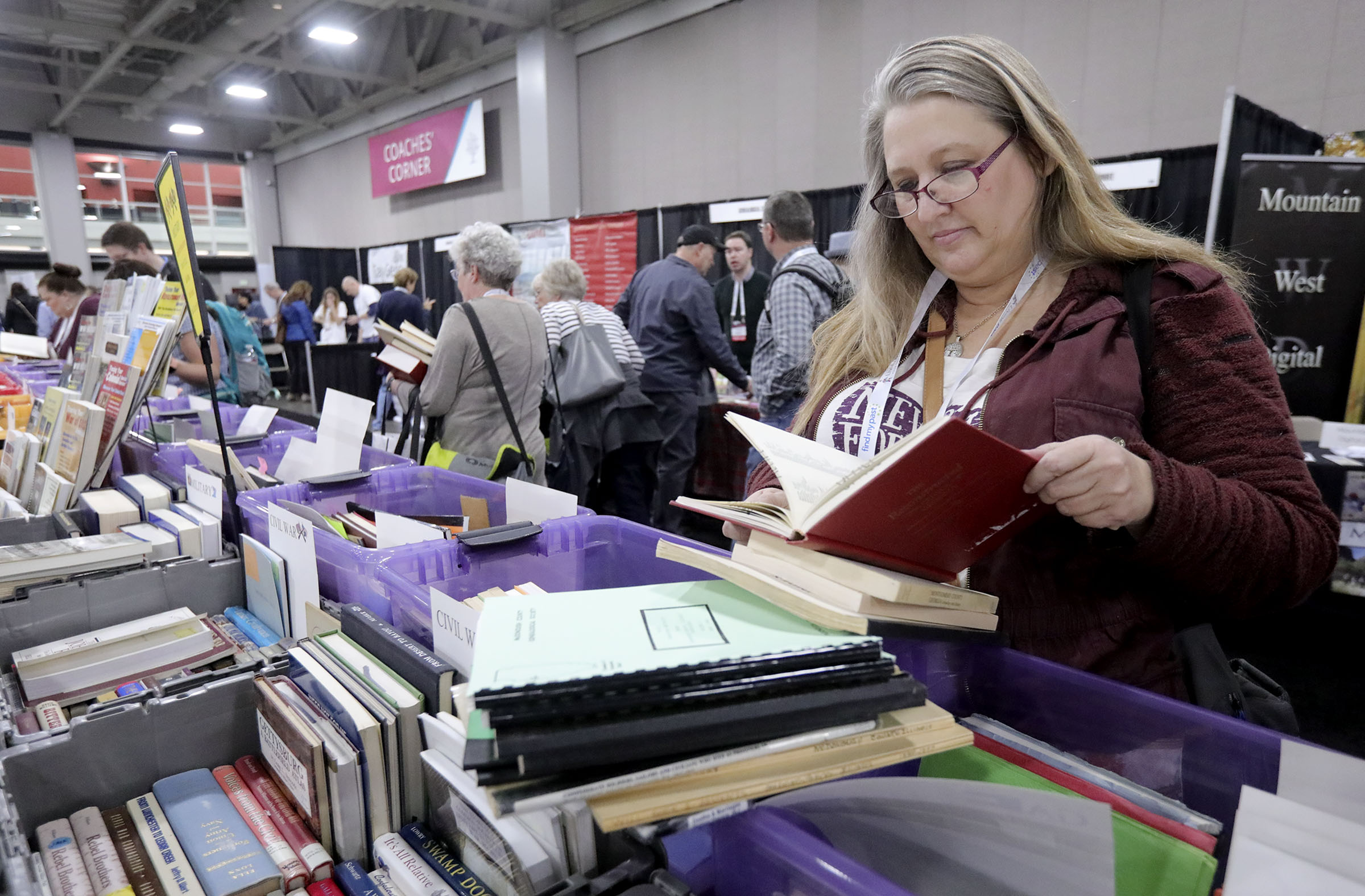 Valerie Luoma looks at historical books that are no longer in print for family history research during RootsTech at the Salt Palace Convention Center in Salt Lake City on Thursday, Feb. 28, 2019.