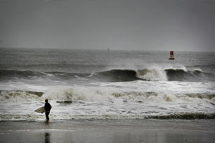 Todd Jarvis of Virginia Beach emerges from the surf after he decided that the currents were too rough as Hurricane Sandy pounded the Virginia coastline, Monday, Oct. 29, 2012 in Virginia Beach, Va.