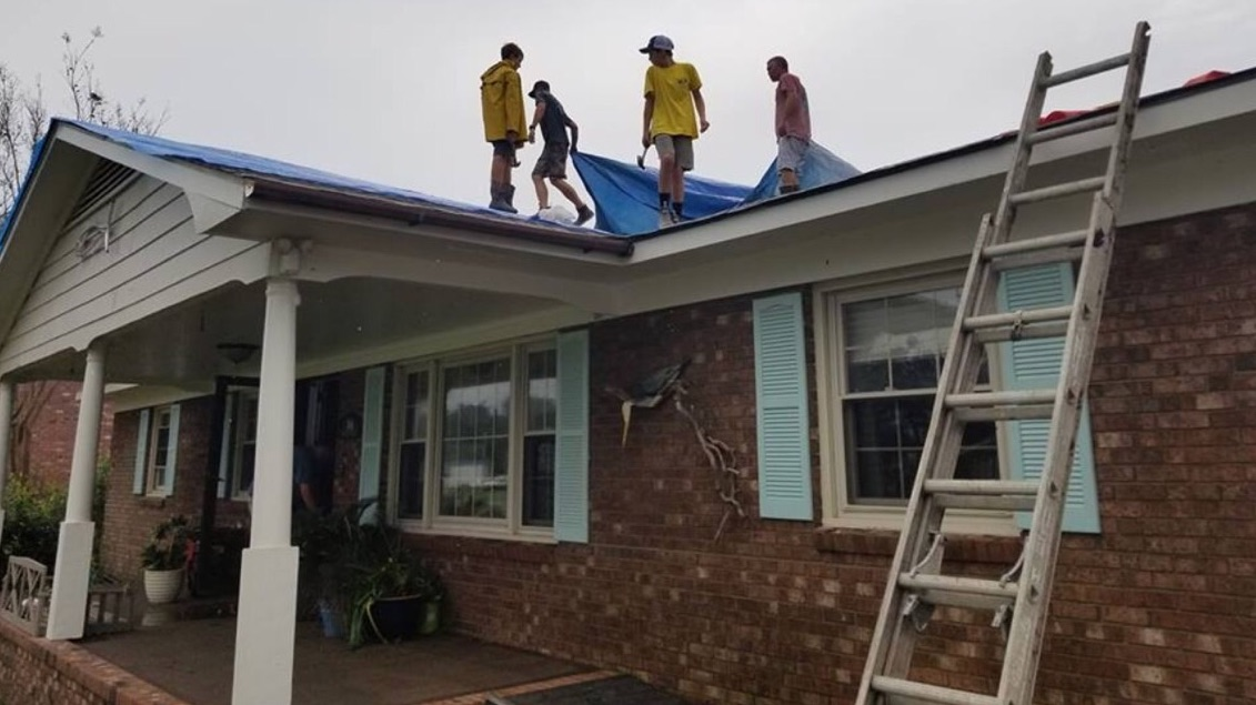 Members clad in yellow Helping Hands vests help repair the roof of a damaged home on Harkers Island, North Carolina, following Hurricane Florence. Local Relief Society and priesthood leaders joined forces to minister to members in need.