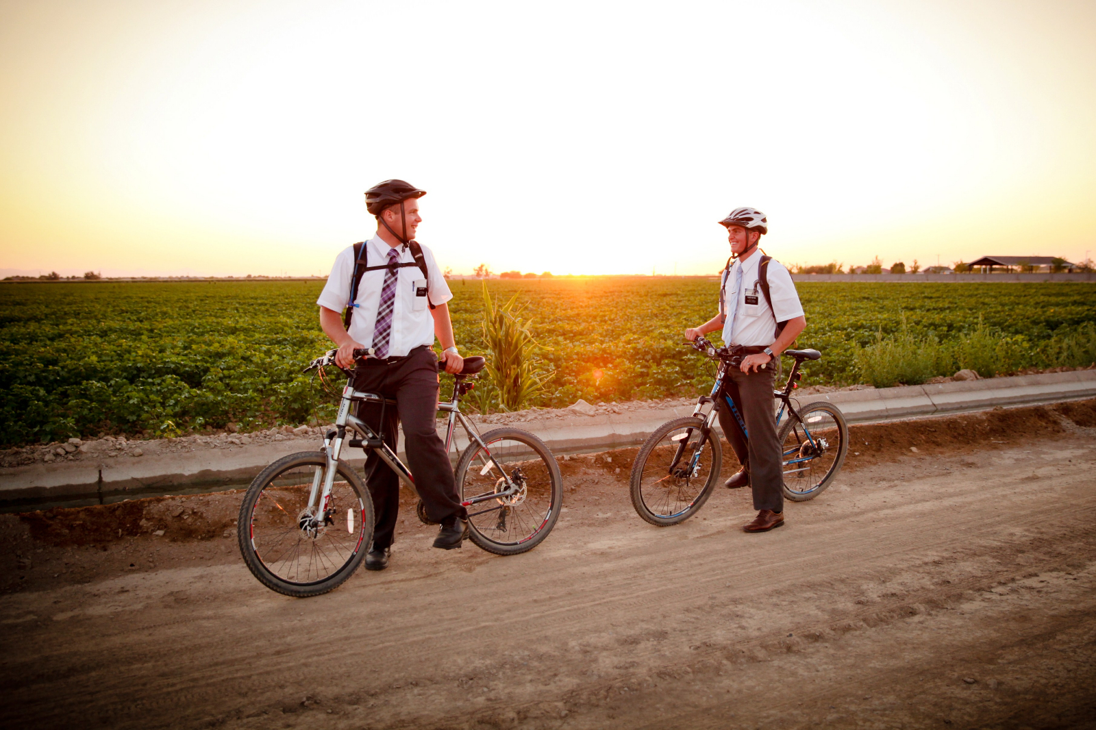 Two missionaries of The Church of Jesus Christ of Latter-day Saints ride their bicycles.